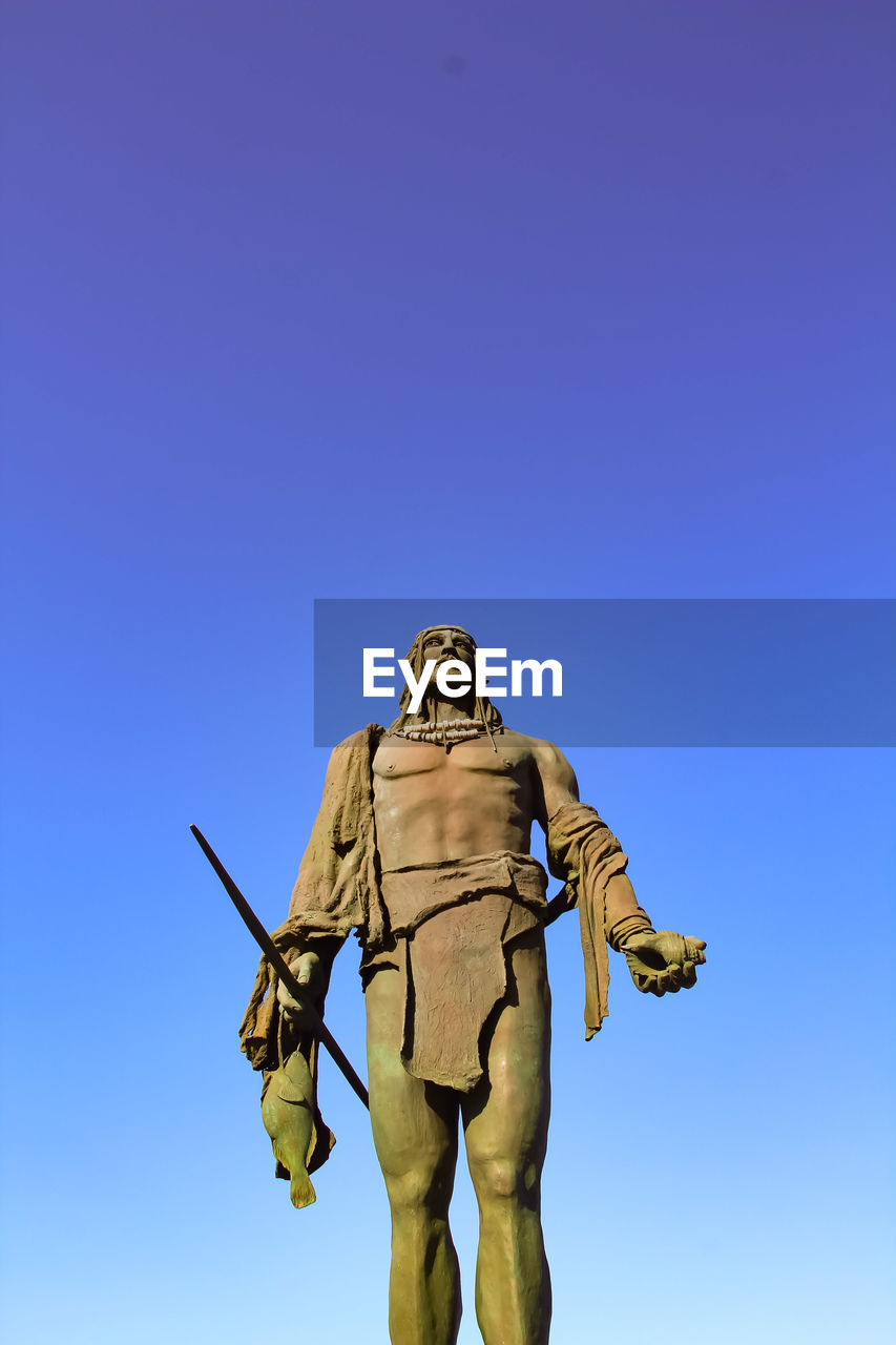 human representation, male likeness, sky, representation, art and craft, low angle view, clear sky, statue, blue, sculpture, nature, no people, creativity, day, craft, copy space, outdoors, history, religion, sunlight