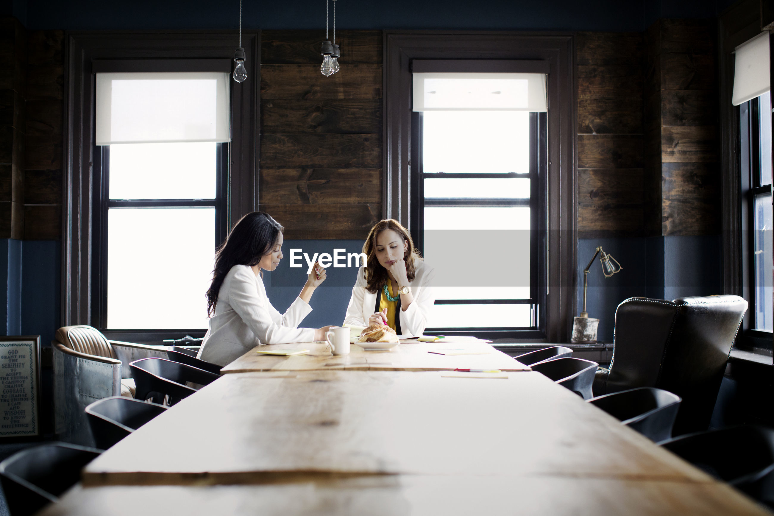 Businesswomen discussing while sitting at desk in office