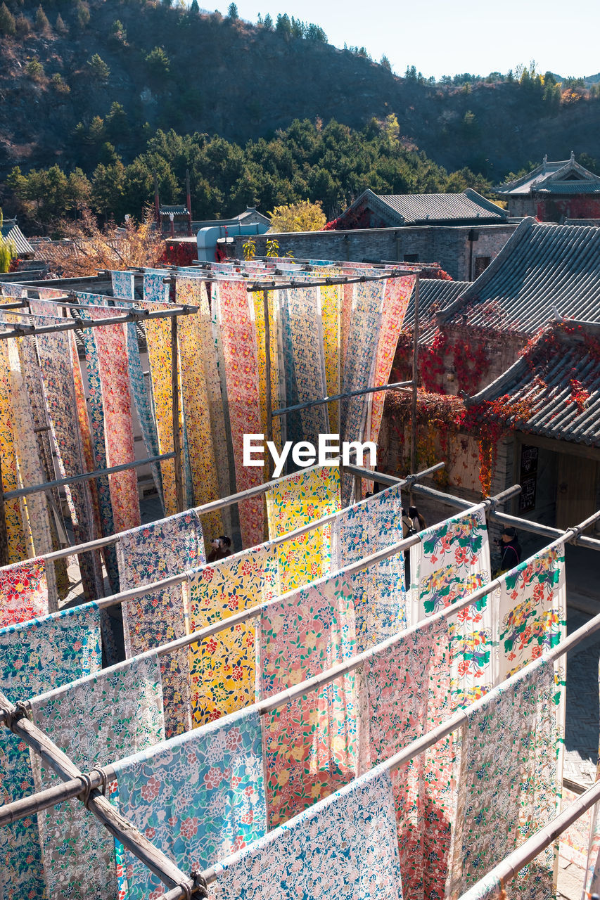 HIGH ANGLE VIEW OF MULTI COLORED HOUSE BY BUILDING