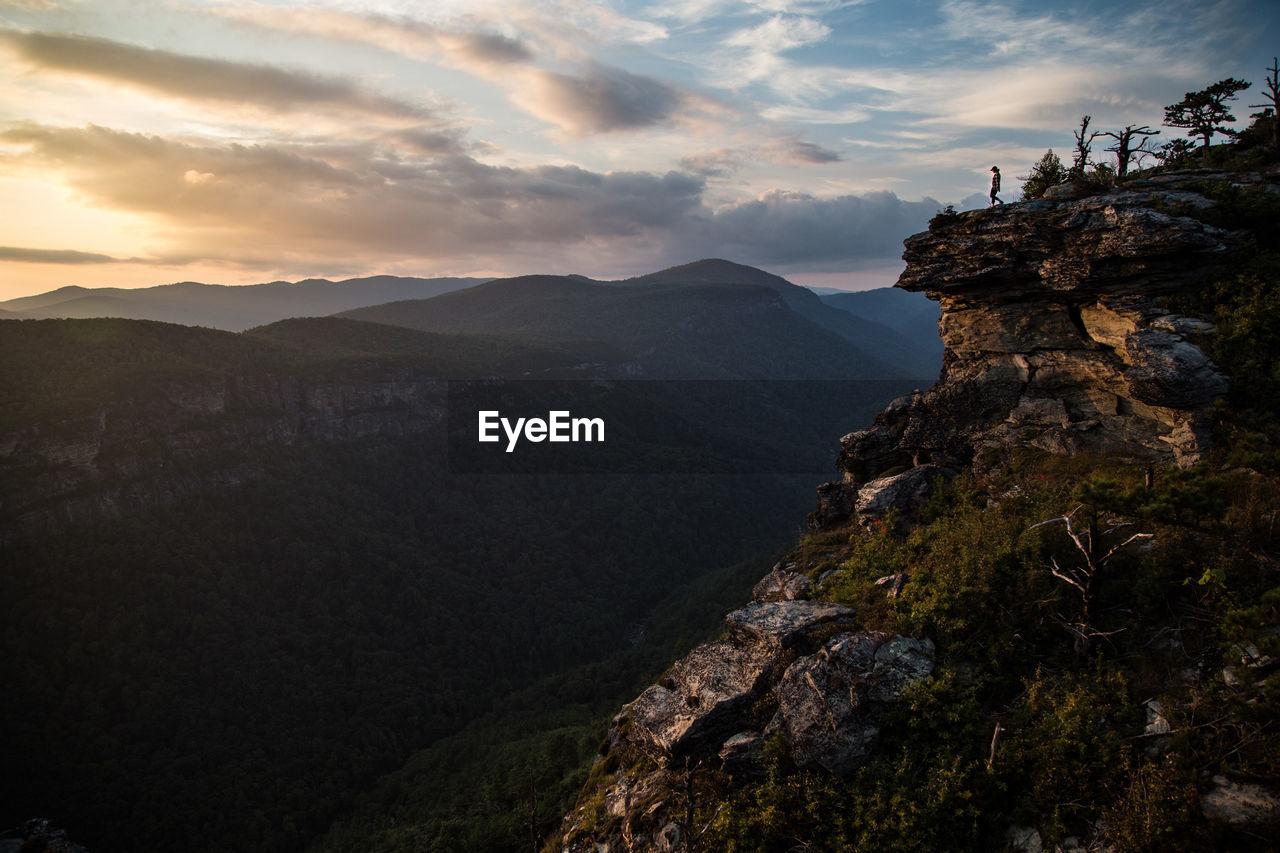 mountain, sky, beauty in nature, nature, cloud - sky, environment, adventure, scenics - nature, tranquil scene, tranquility, mountain range, sunset, landscape, idyllic, land, rock, leisure activity, high, activity, people, mountain peak
