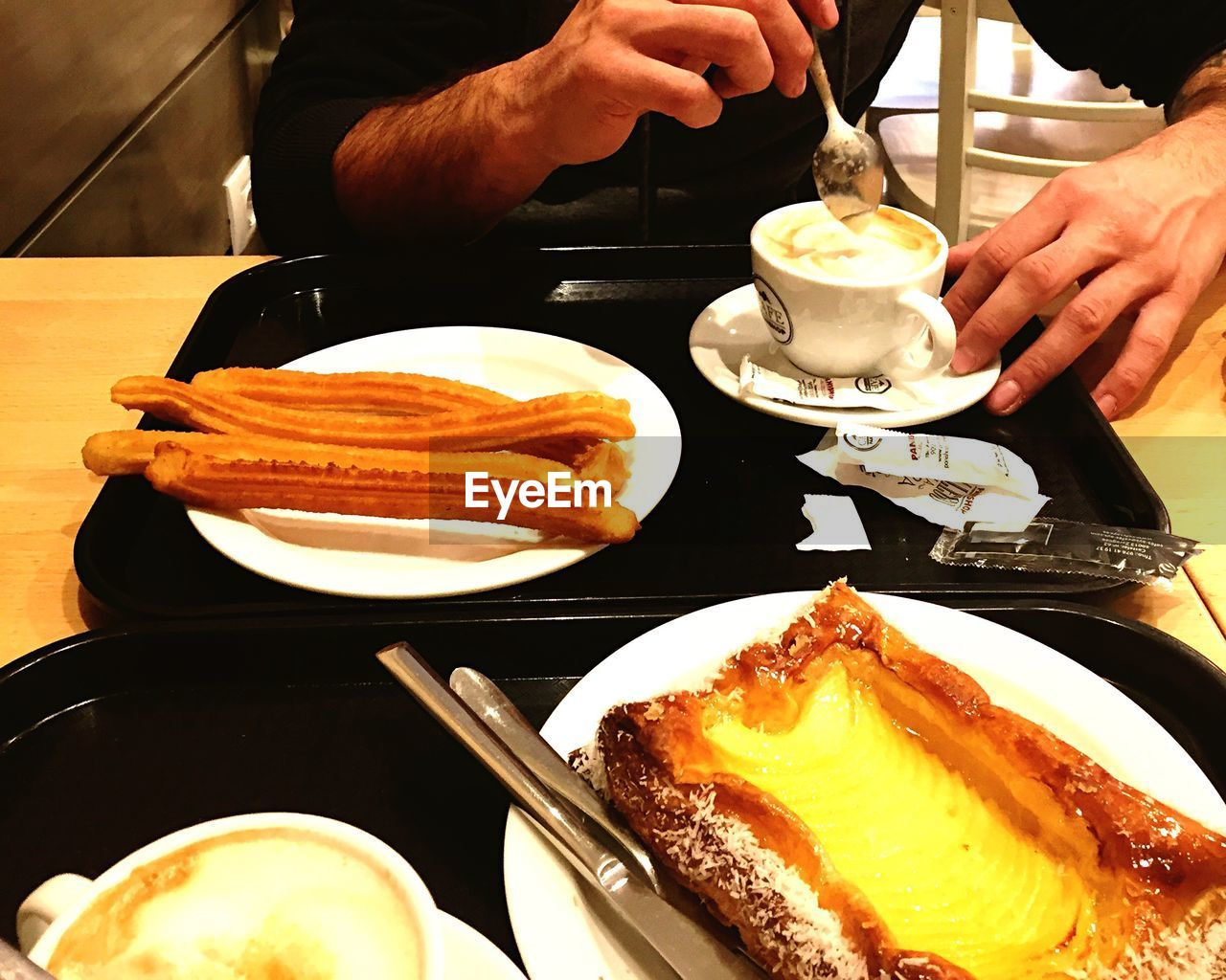 food and drink, plate, human hand, freshness, food, table, indoors, real people, coffee cup, temptation, refreshment, coffee - drink, dessert, ready-to-eat, holding, drink, sweet food, indulgence, serving size, close-up, unhealthy eating, one person, human body part, cappuccino, pancake, men, day