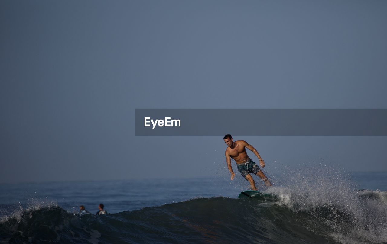sea, water, real people, leisure activity, sky, lifestyles, copy space, men, clear sky, nature, beauty in nature, shirtless, people, land, scenics - nature, day, motion, beach, sport, horizon over water, outdoors