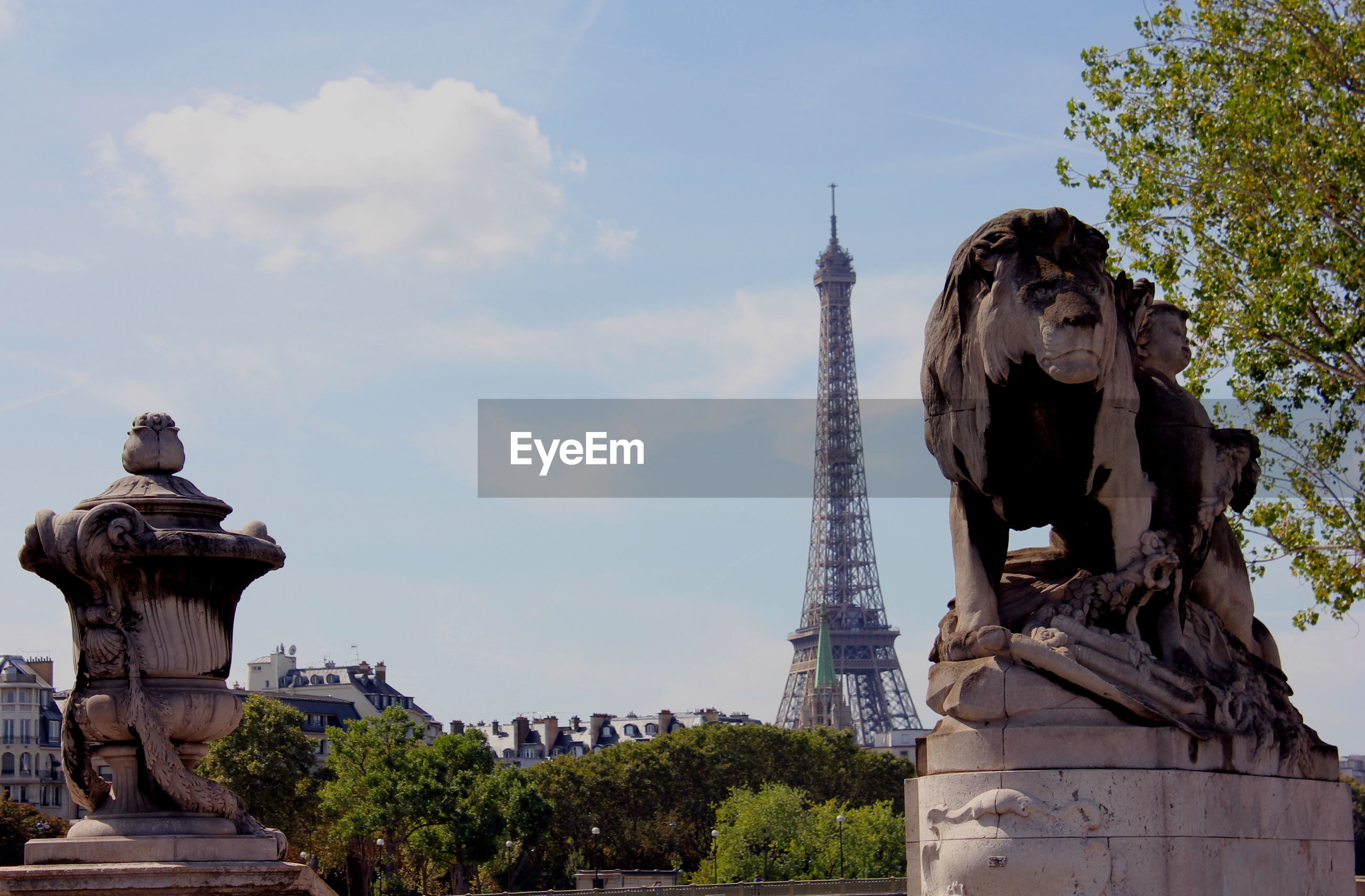 Lion statue against eiffel tower in city
