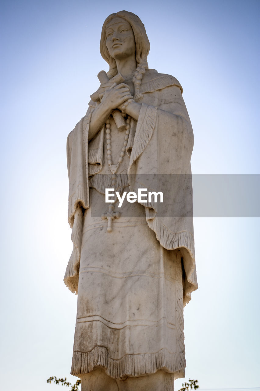 sculpture, human representation, representation, art and craft, statue, male likeness, sky, low angle view, creativity, no people, religion, craft, architecture, spirituality, day, nature, belief, carving - craft product, clear sky
