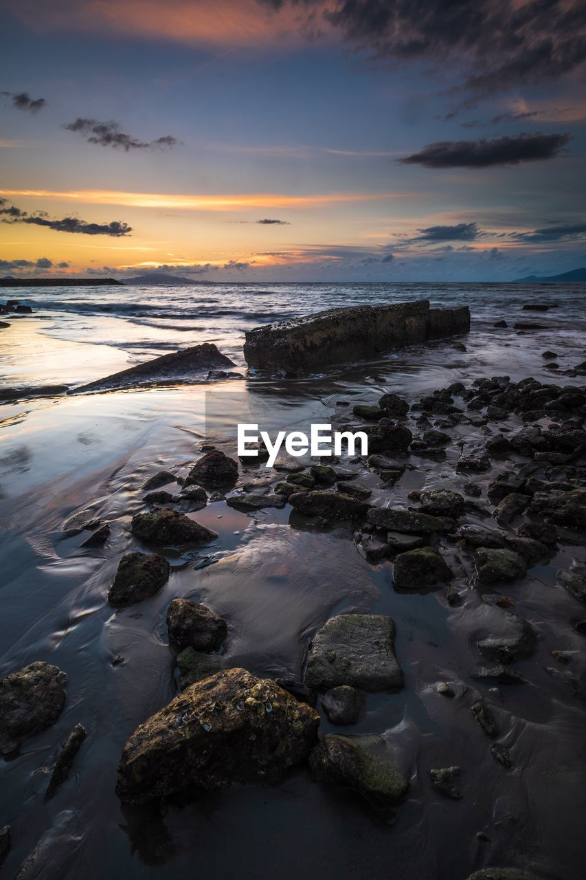 sky, water, sunset, beauty in nature, sea, scenics - nature, rock, solid, beach, cloud - sky, rock - object, land, horizon over water, nature, no people, horizon, tranquility, motion, tranquil scene