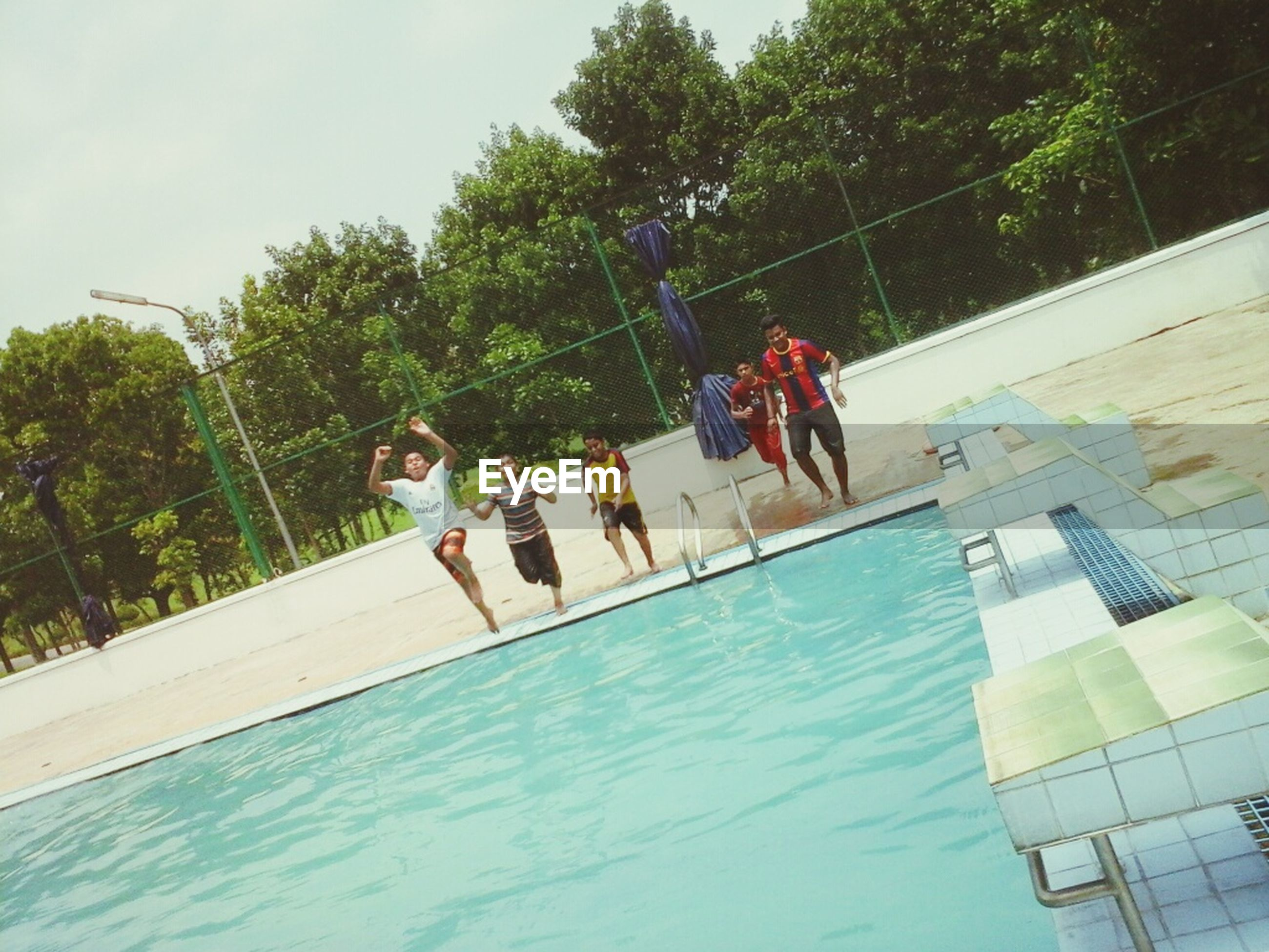 leisure activity, lifestyles, water, men, enjoyment, jumping, tree, full length, waterfront, fun, togetherness, sport, boys, vacations, motion, playing, shirtless