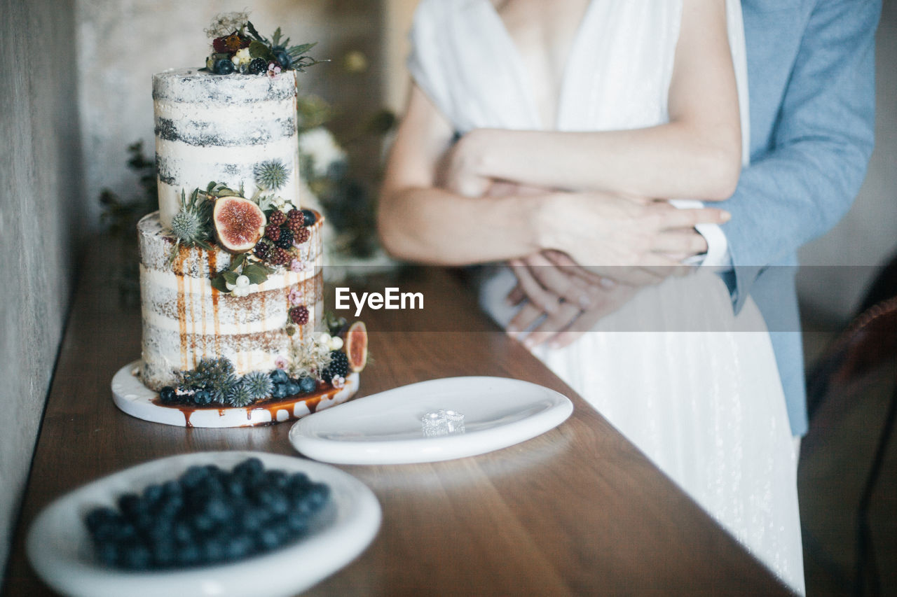 Midsection Of Couple With Cake On Table