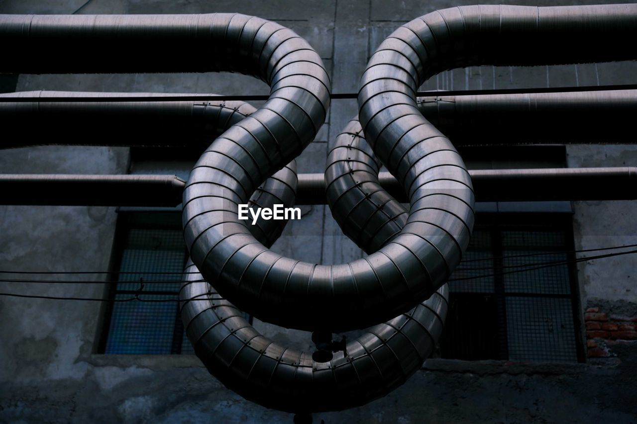 Low Angle View Of Air Ducts Against Old Factory