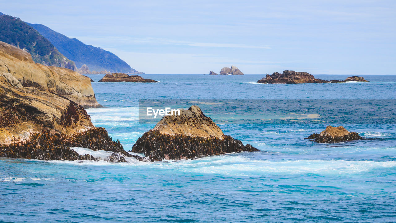 water, sea, scenics - nature, beauty in nature, waterfront, rock, sky, tranquil scene, tranquility, day, rock - object, no people, solid, nature, rock formation, land, blue, idyllic, beach, outdoors, horizon over water, turquoise colored, rocky coastline, stack rock