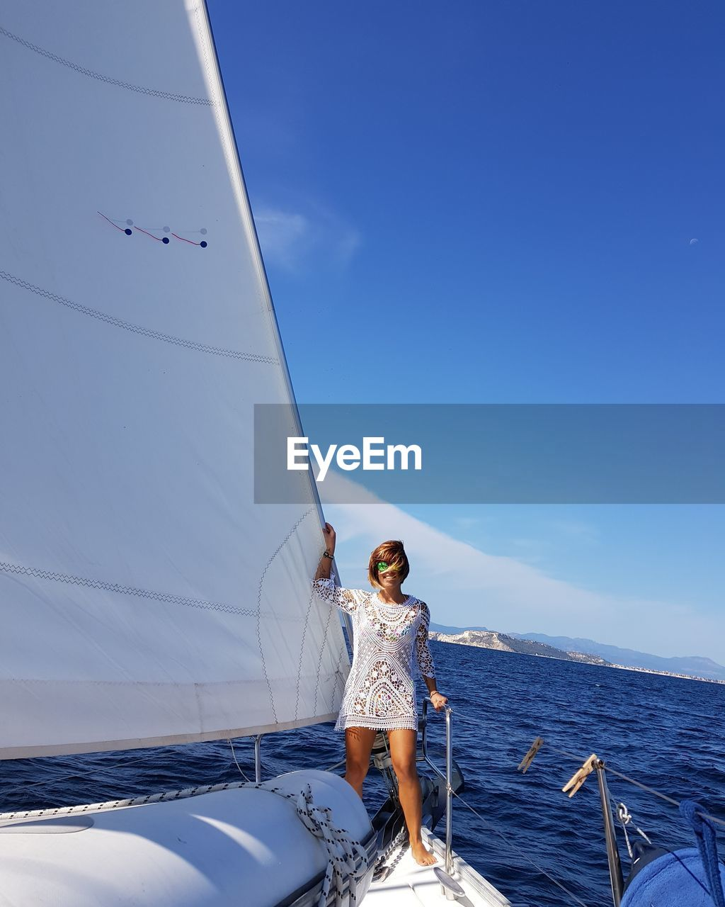 Woman Standing On Sailboat In Sea Against Blue Sky