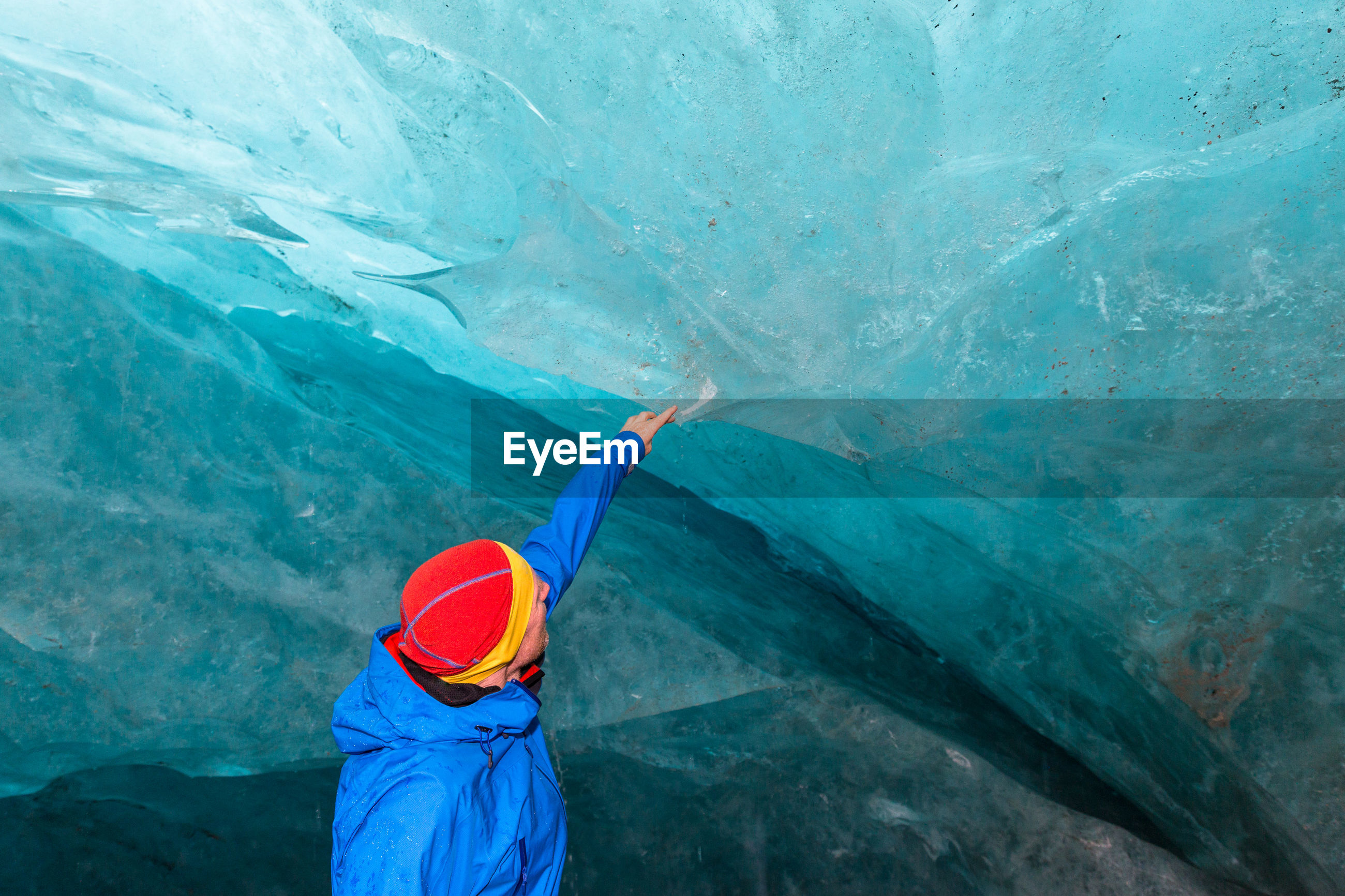 Man touching turquoise glacier at cave