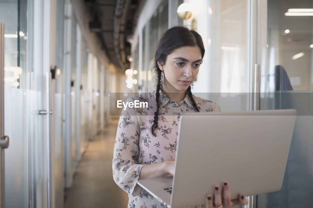 laptop, wireless technology, one person, using laptop, technology, front view, computer, communication, young adult, young women, women, adult, connection, real people, indoors, waist up, sitting, beautiful woman, focus on foreground, hairstyle