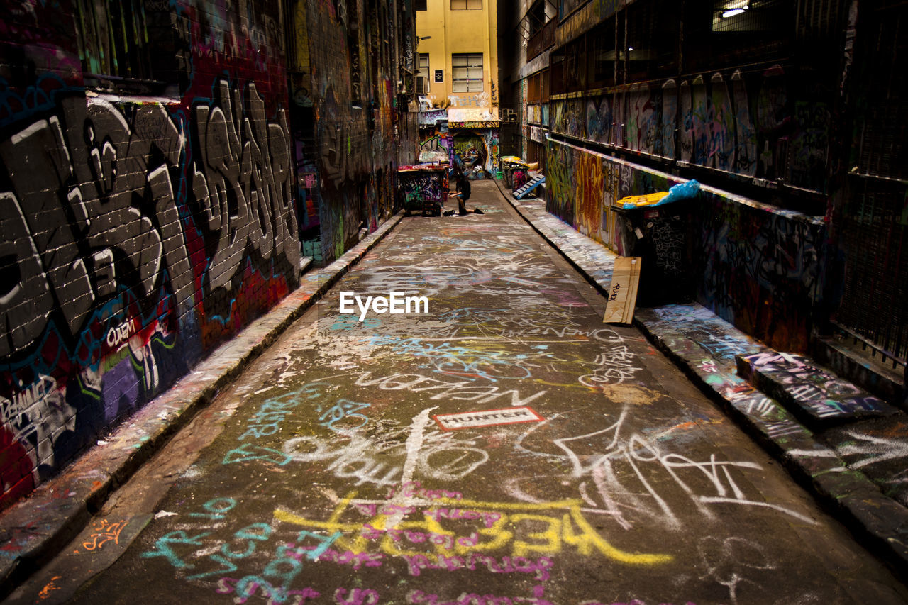 architecture, graffiti, building exterior, city, multi colored, creativity, the way forward, text, built structure, incidental people, wall - building feature, direction, art and craft, street, day, choice, communication, diminishing perspective, people, alley
