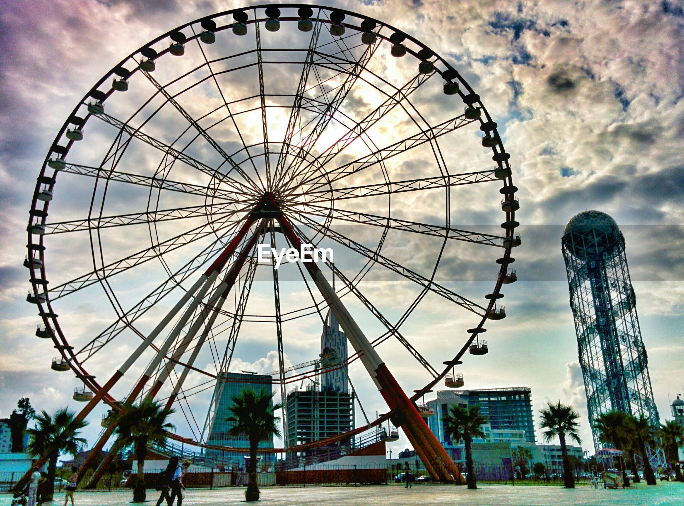 Huge ferris wheel against cloudy sky