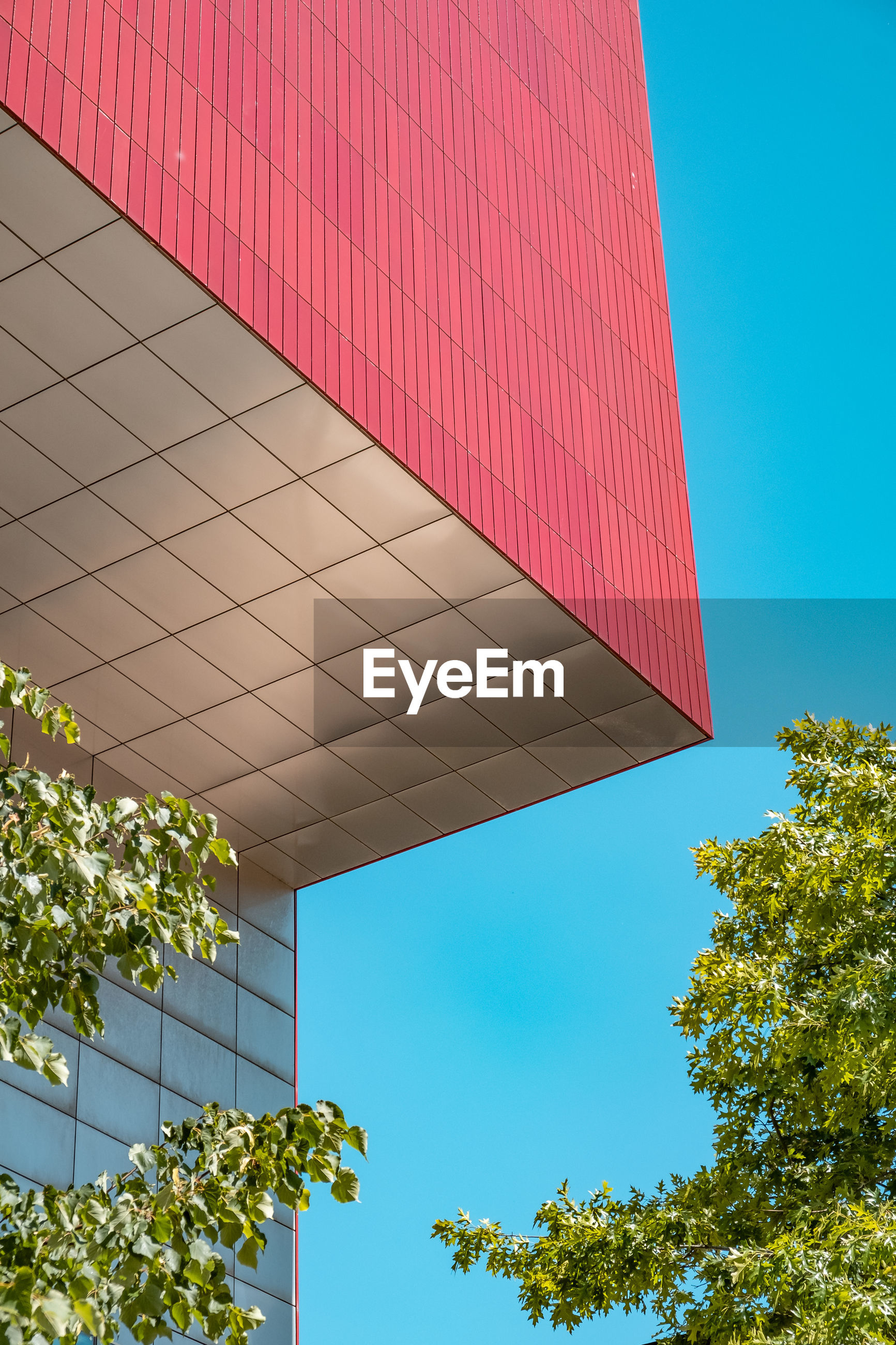 Red angular building against blue sky and trees