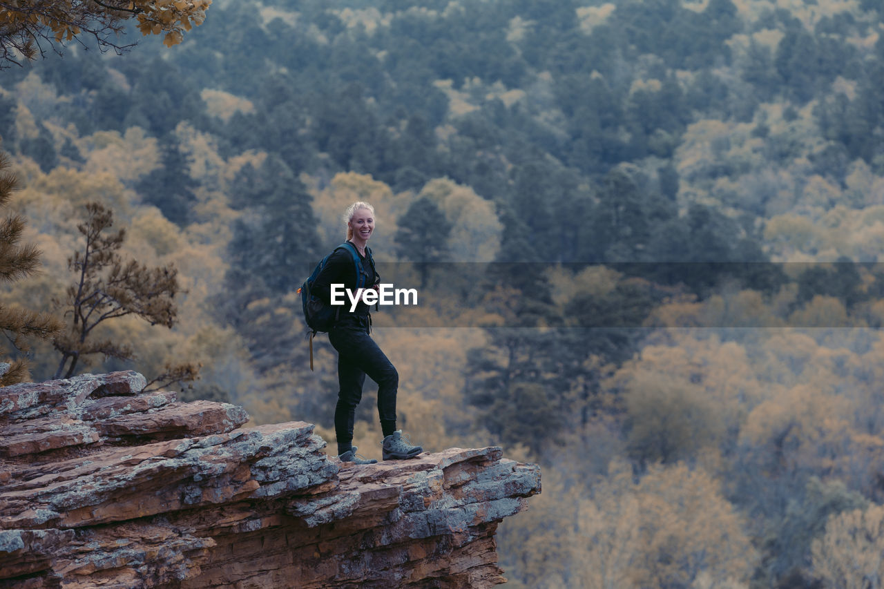 FULL LENGTH OF MAN STANDING ON ROCK AT FOREST