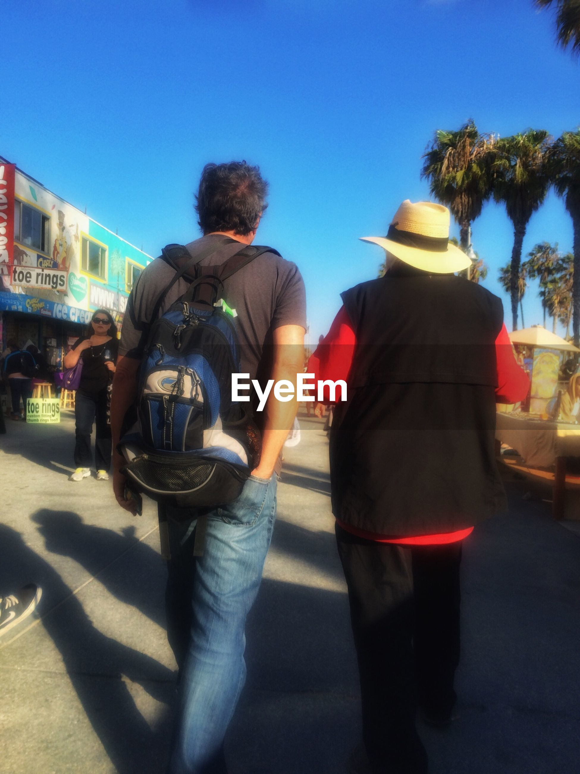lifestyles, men, leisure activity, clear sky, togetherness, rear view, casual clothing, transportation, full length, bonding, mode of transport, person, land vehicle, blue, walking, sunlight