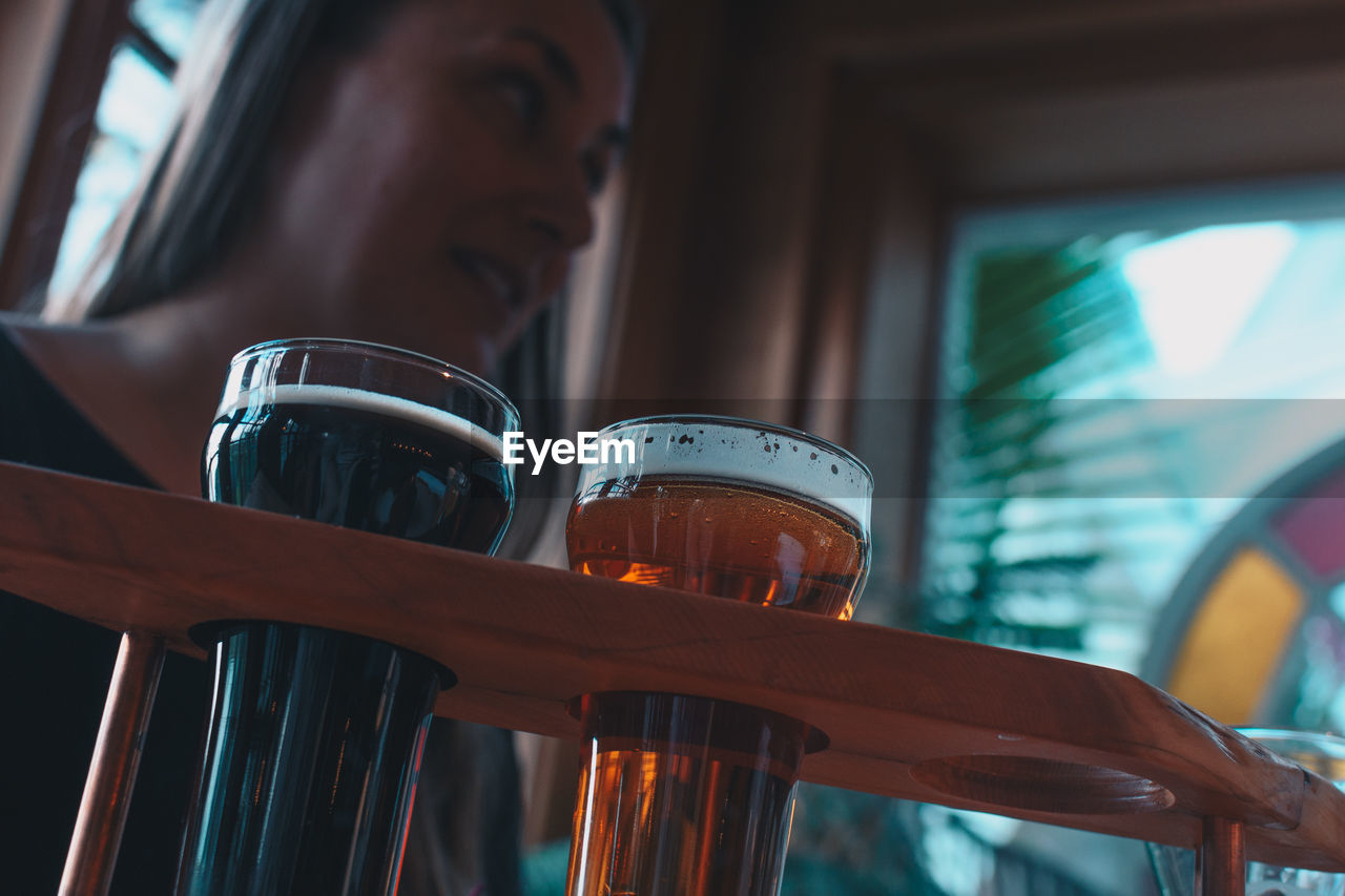 Low angle view of craft beer with woman in background at bar