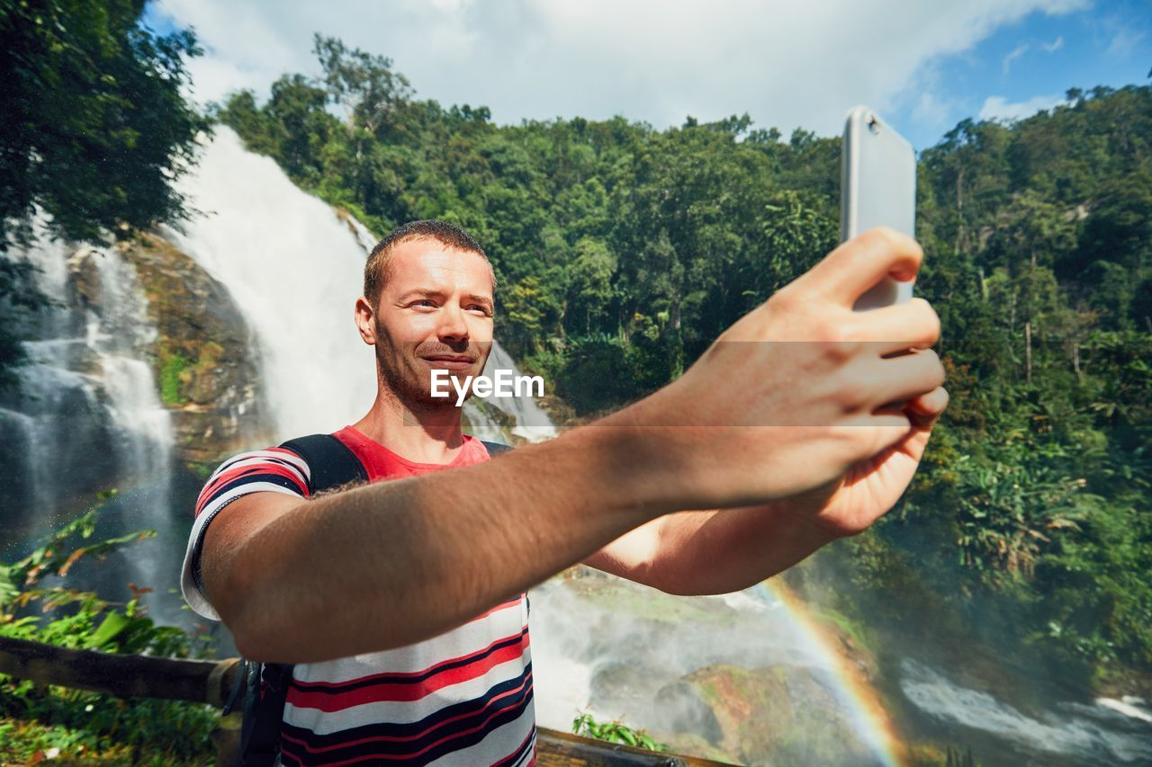 Man Taking Selfie While Standing Against Waterfall