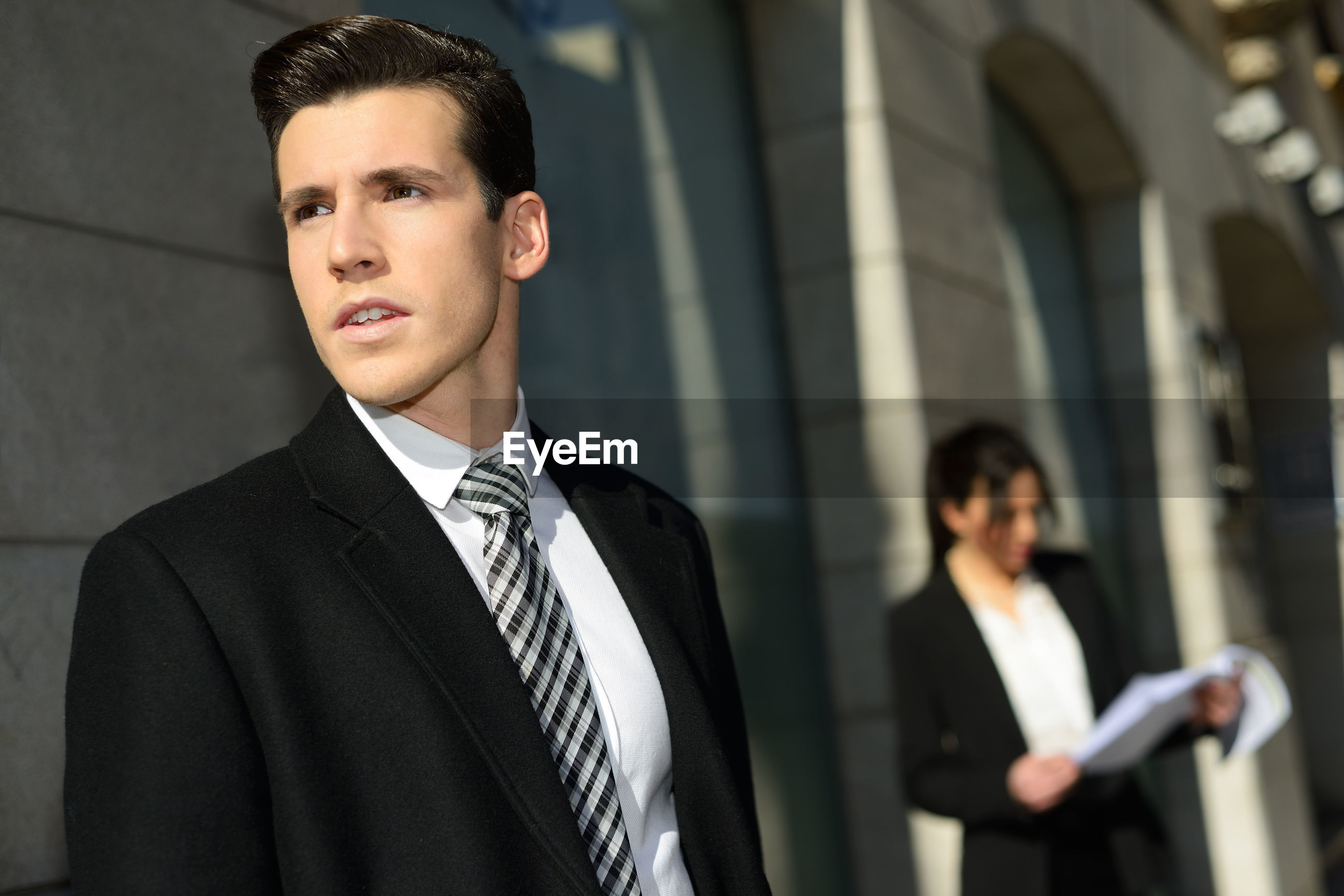 Close-up of businessman standing with female coworker in city