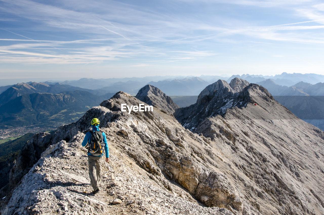 Rear View Of Hiker Walking On Mountain
