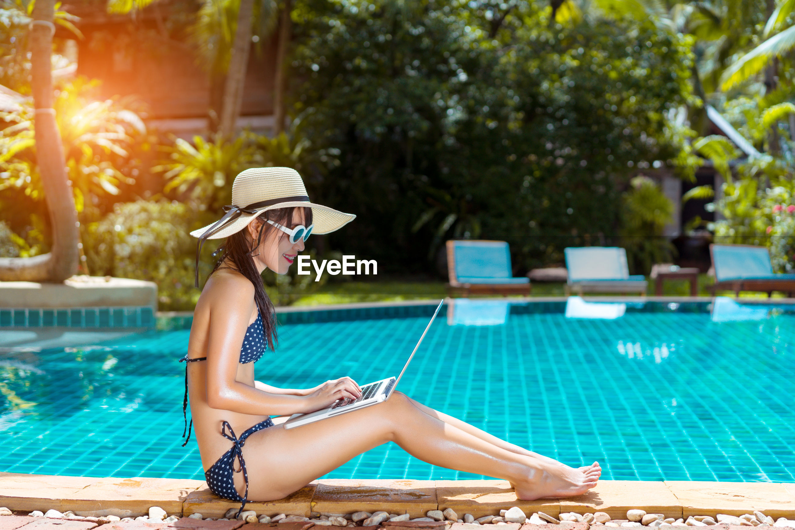 Side view of young woman typing on laptop while sitting on poolside