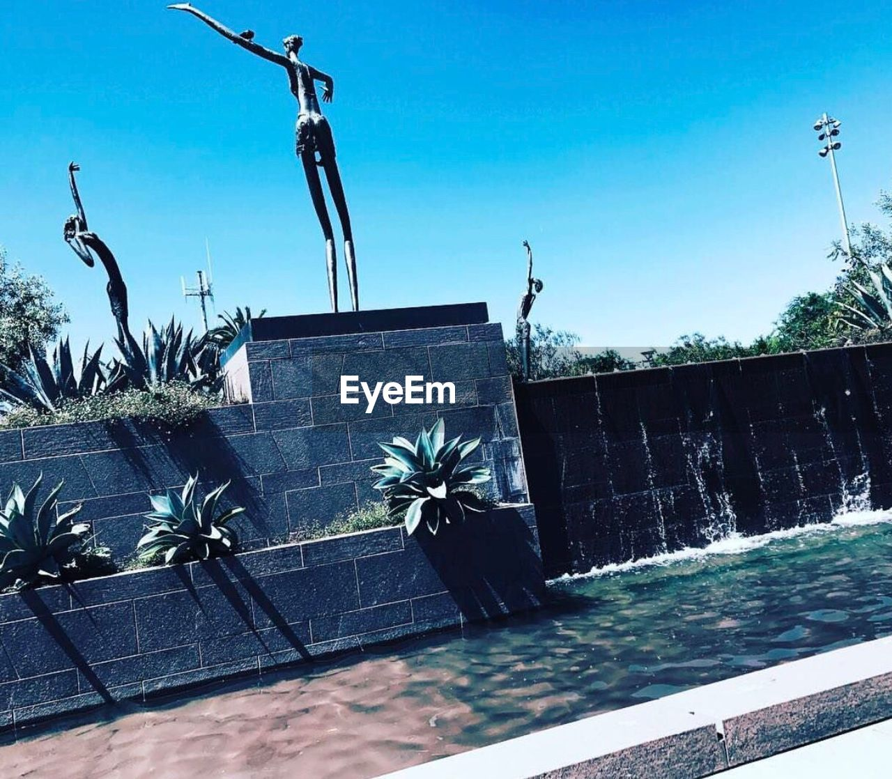 clear sky, day, outdoors, statue, no people, built structure, blue, tree, building exterior, architecture, sculpture, water, swimming pool, palm tree, sky, nature