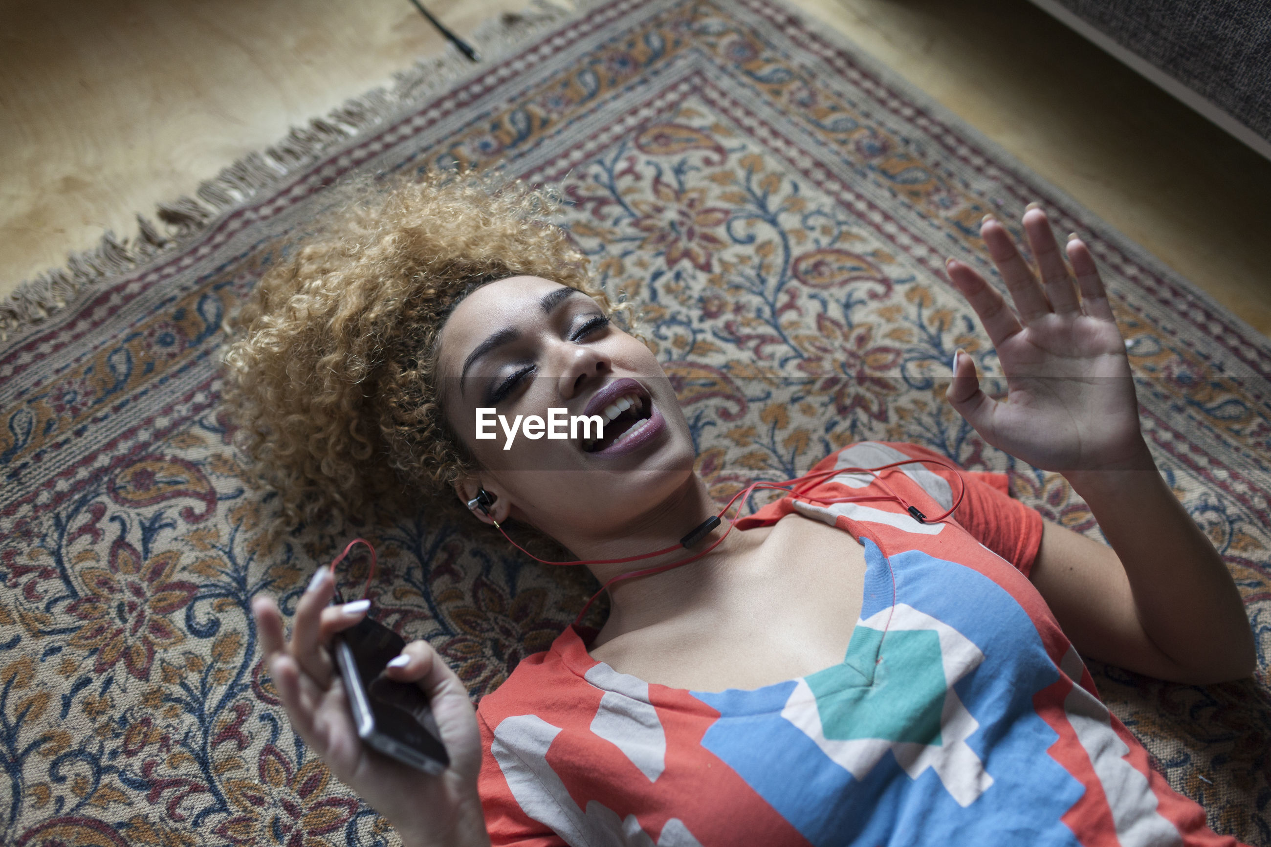 HIGH ANGLE VIEW OF SMILING WOMAN LYING DOWN ON FLOOR