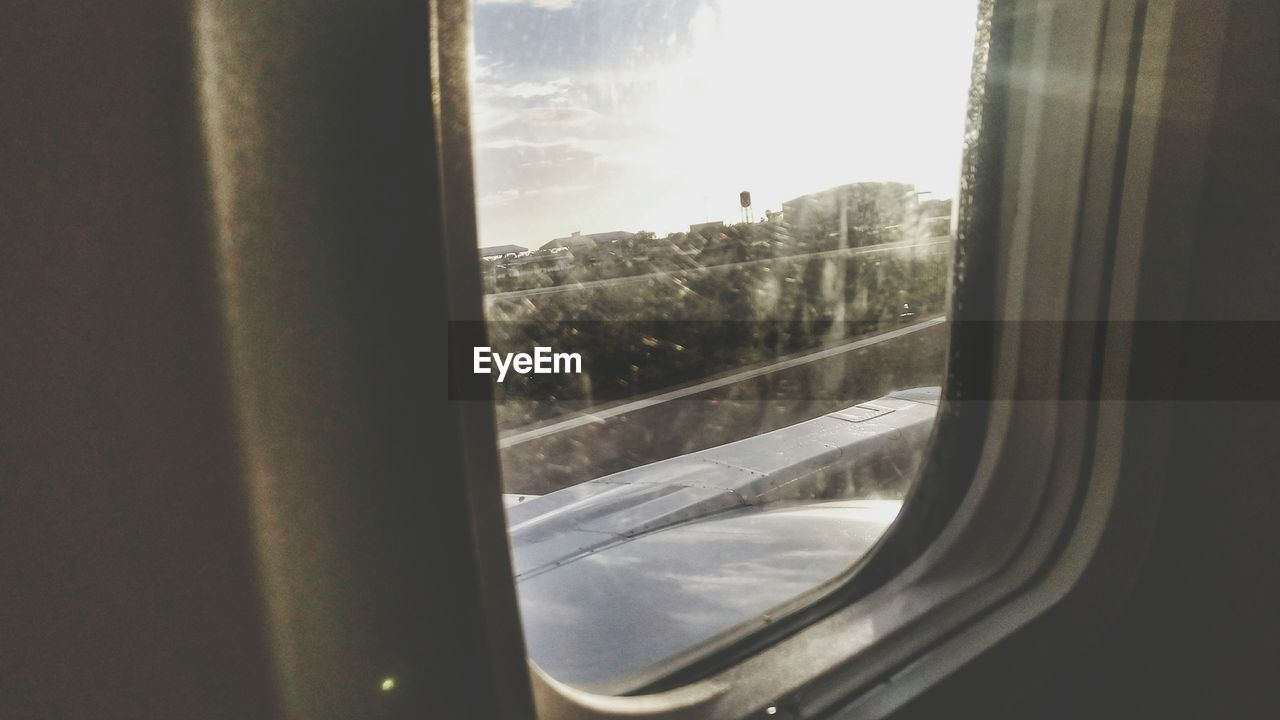 window, transparent, glass - material, vehicle interior, looking through window, indoors, landscape, tree, transportation, mode of transport, nature, no people, day, sky, scenics, close-up, journey, snow, mountain, beauty in nature, winter, airplane