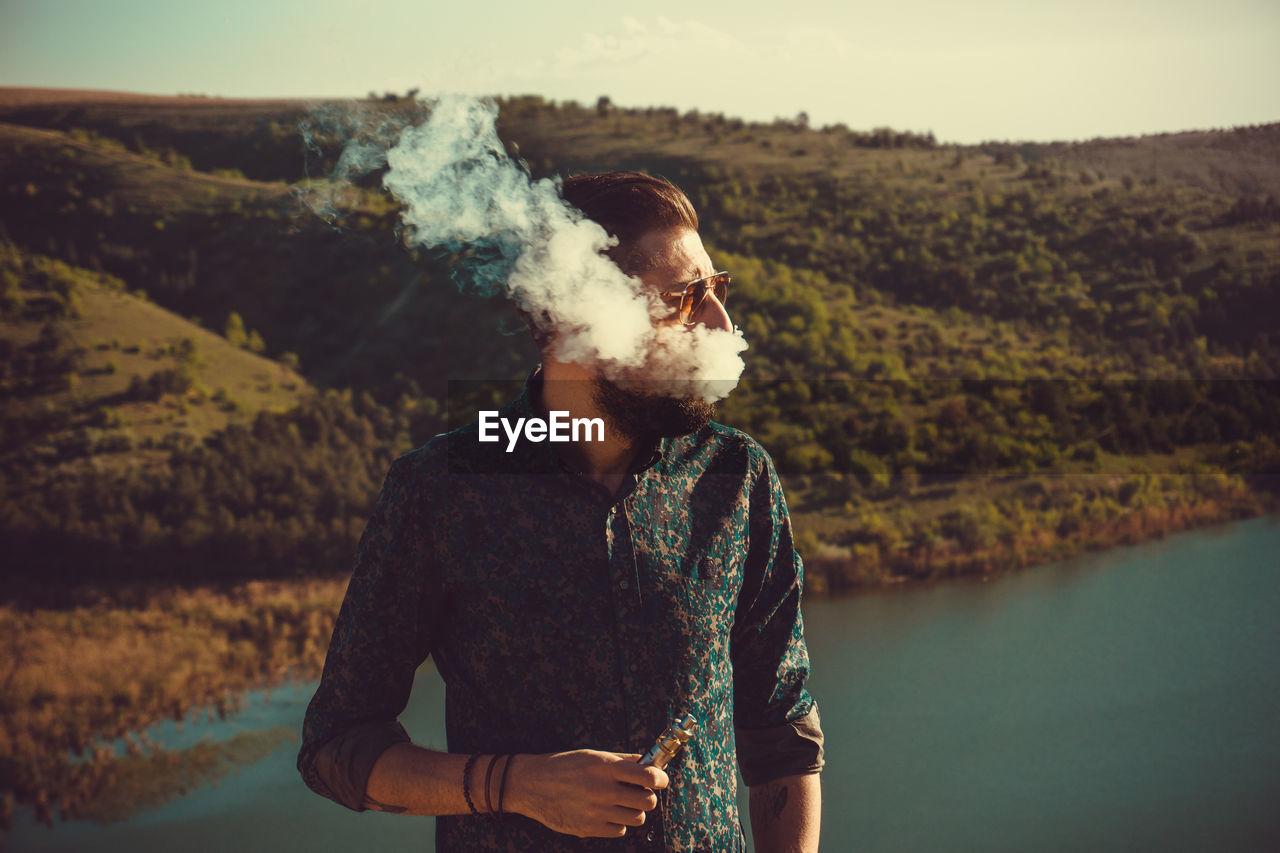 Man Smoking While Standing By Lake