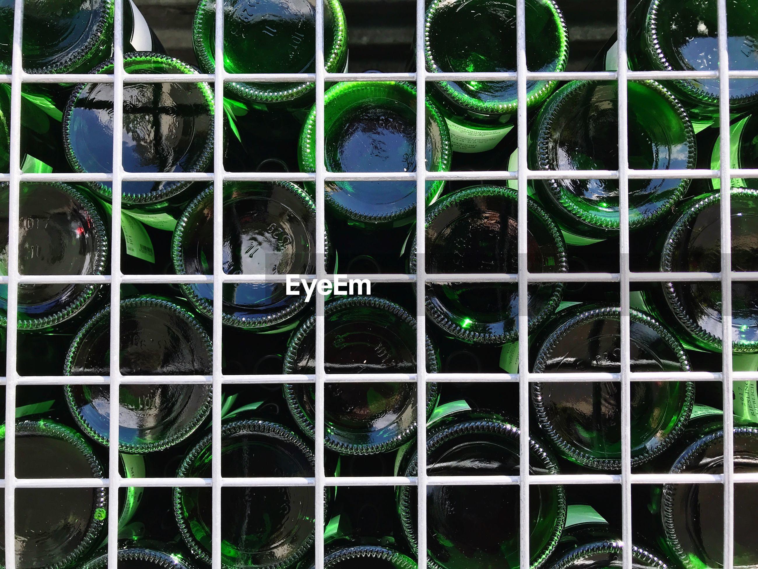 Close-up of bottles seen through metal grate