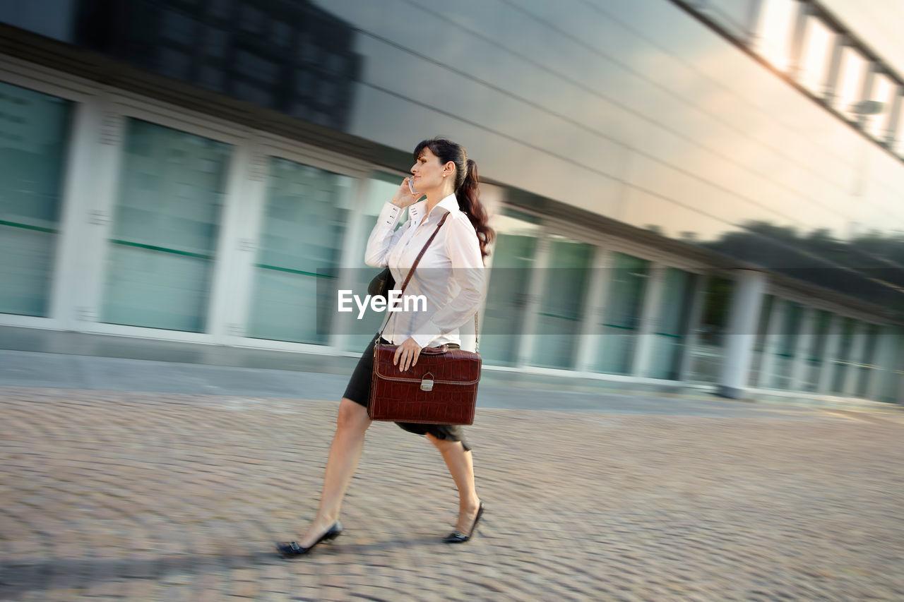 FULL LENGTH OF WOMAN WITH UMBRELLA WALKING ON FLOOR