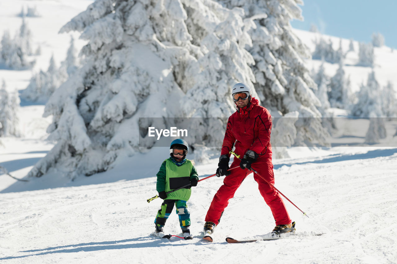 Full length of father and son skiing on snow during winter
