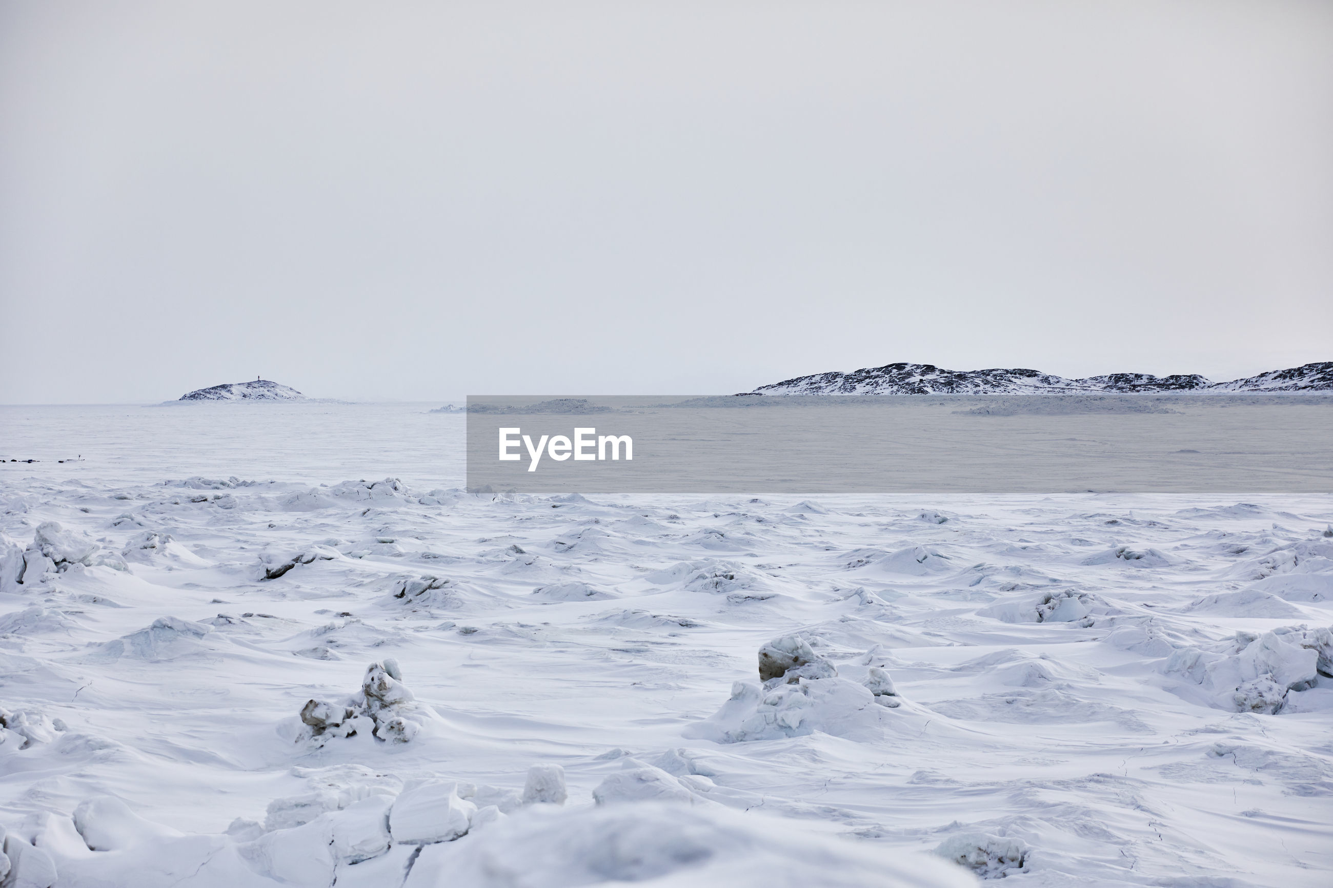 FROZEN SEA AGAINST CLEAR SKY DURING WINTER