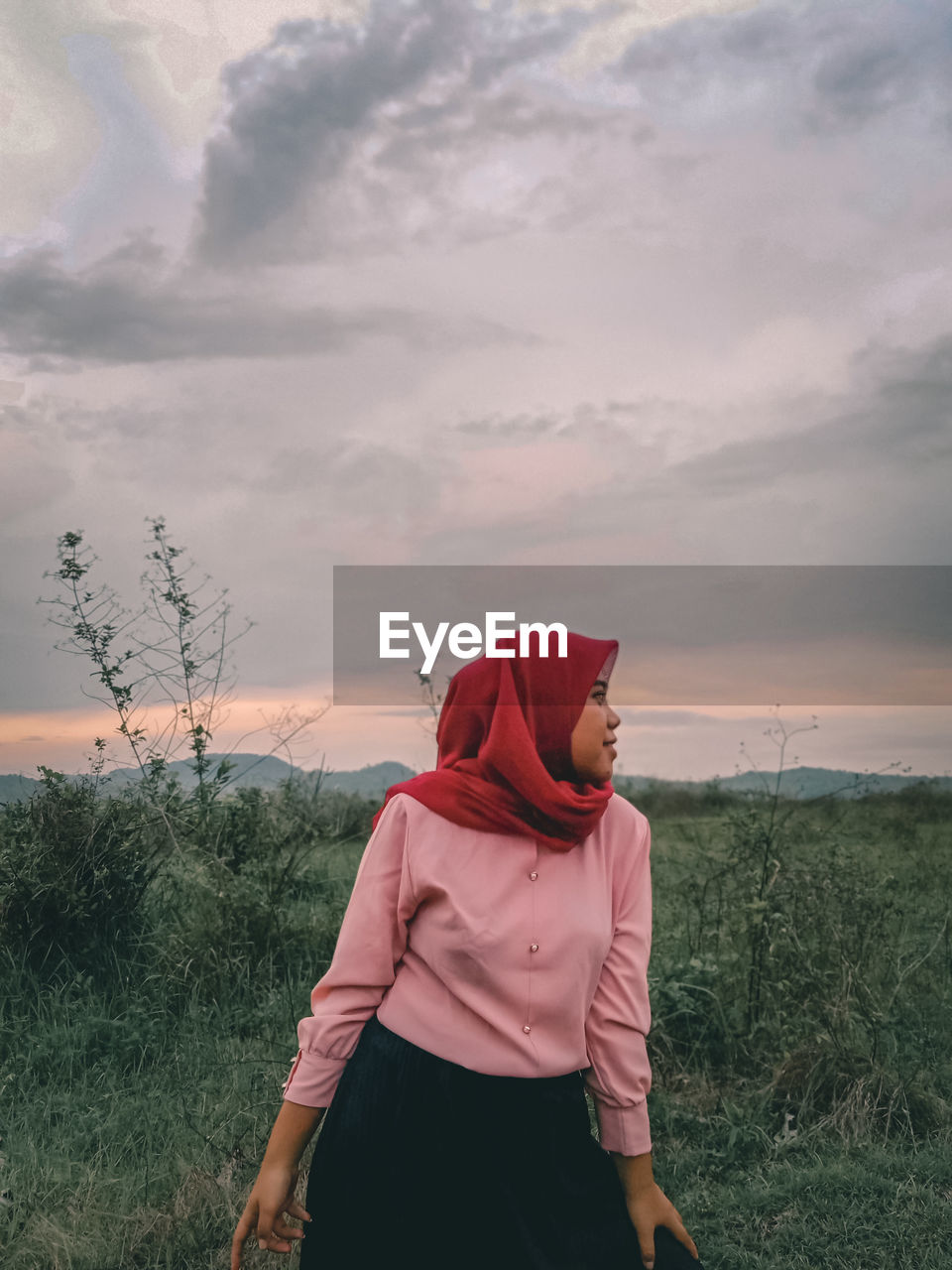 Woman wearing hijab standing on land against cloudy sky during sunset