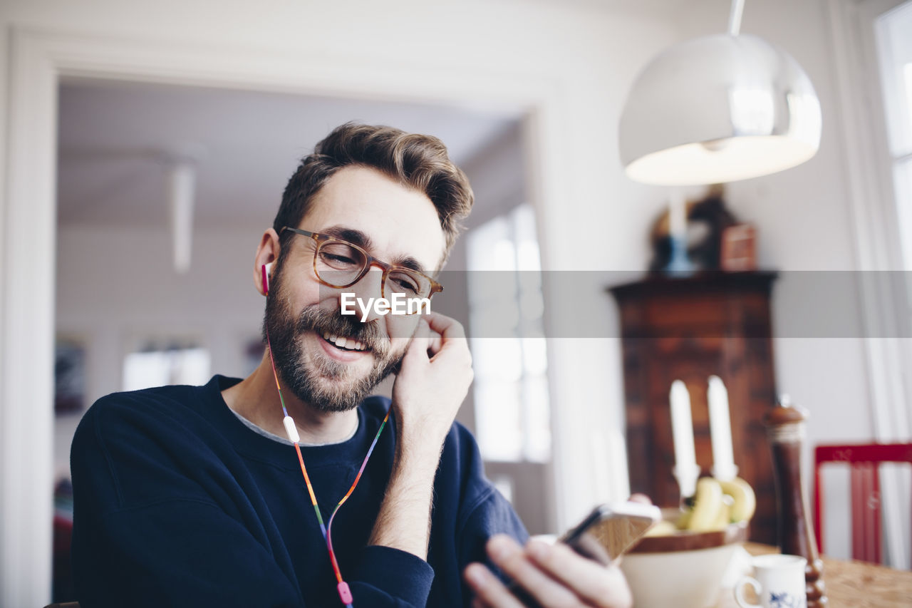 smiling, beard, young adult, one person, facial hair, indoors, happiness, headshot, front view, portrait, young men, lifestyles, focus on foreground, real people, casual clothing, home interior, emotion, communication, wireless technology