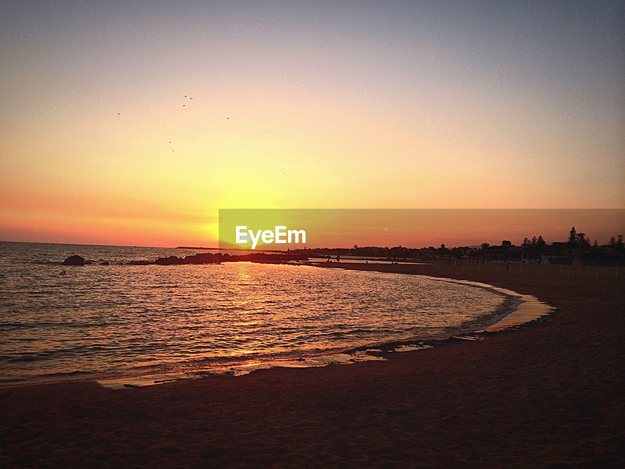 sunset, sea, water, beach, horizon over water, scenics, sun, orange color, tranquil scene, shore, beauty in nature, tranquility, silhouette, bird, idyllic, nature, sand, sky, incidental people, sunlight