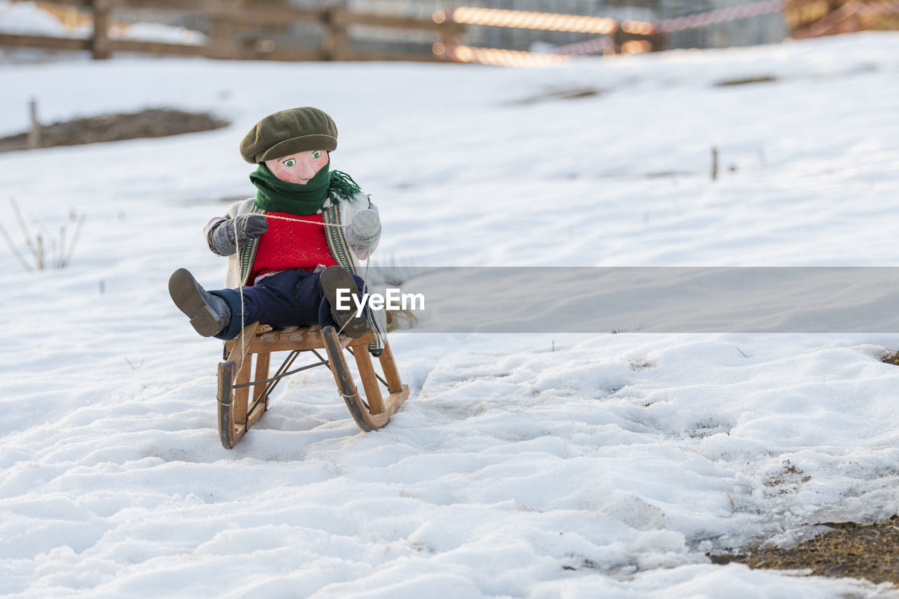 Puppet on snow covered land