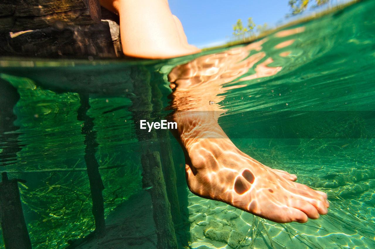 Underwater view of woman legs in plitvice lakes, croatia