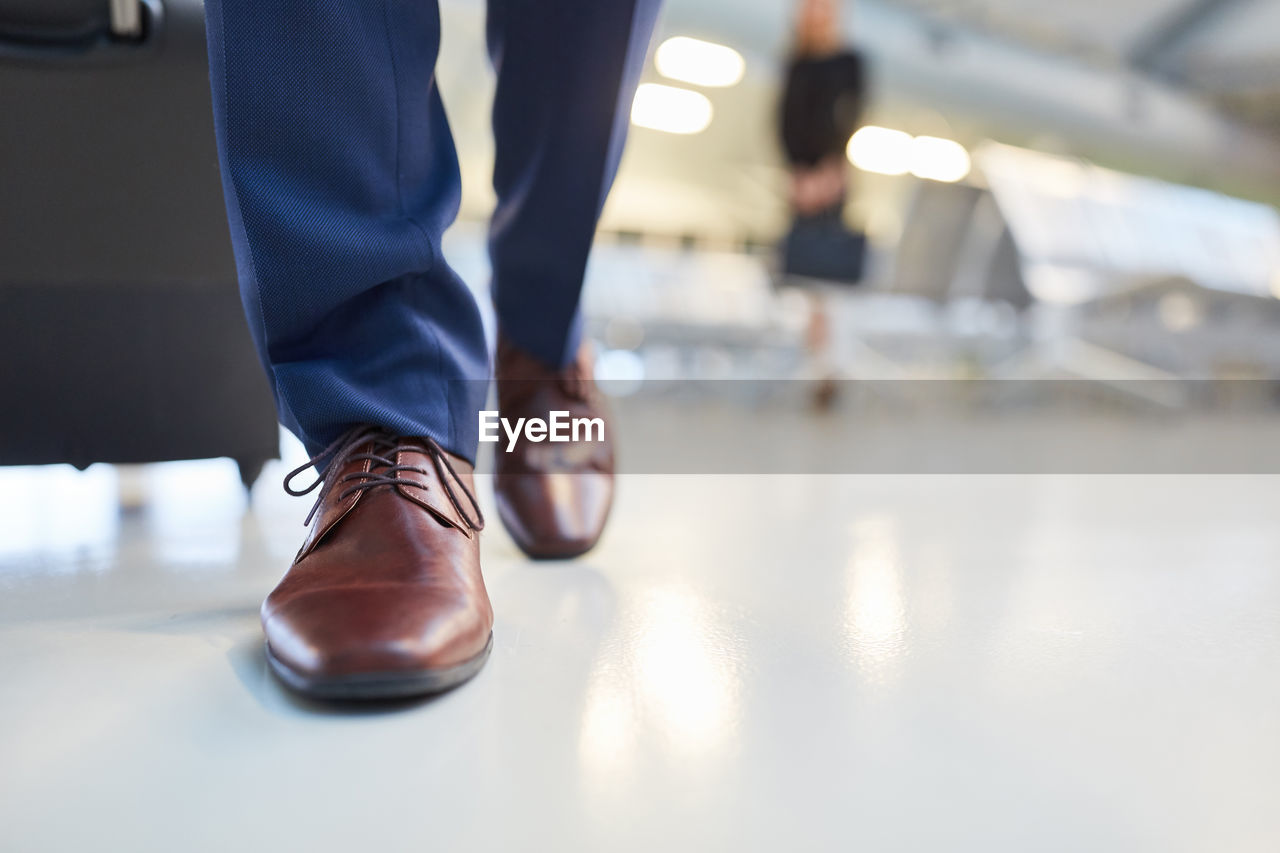shoe, one person, low section, real people, body part, men, human leg, human body part, indoors, business, lifestyles, selective focus, day, flooring, human foot, close-up, focus on foreground, businessman, table, human limb