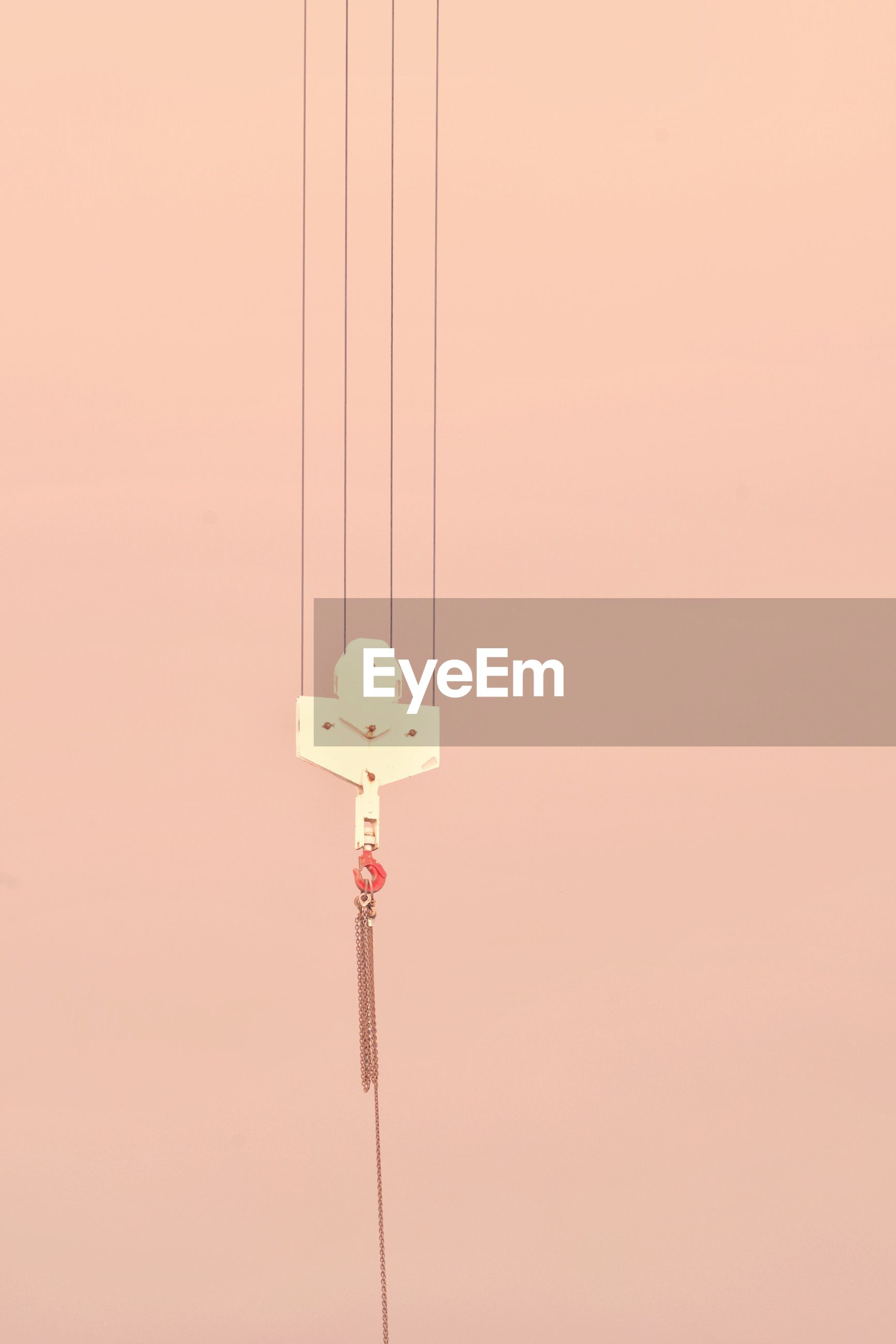Close-up of hook hanging on cable against colored background