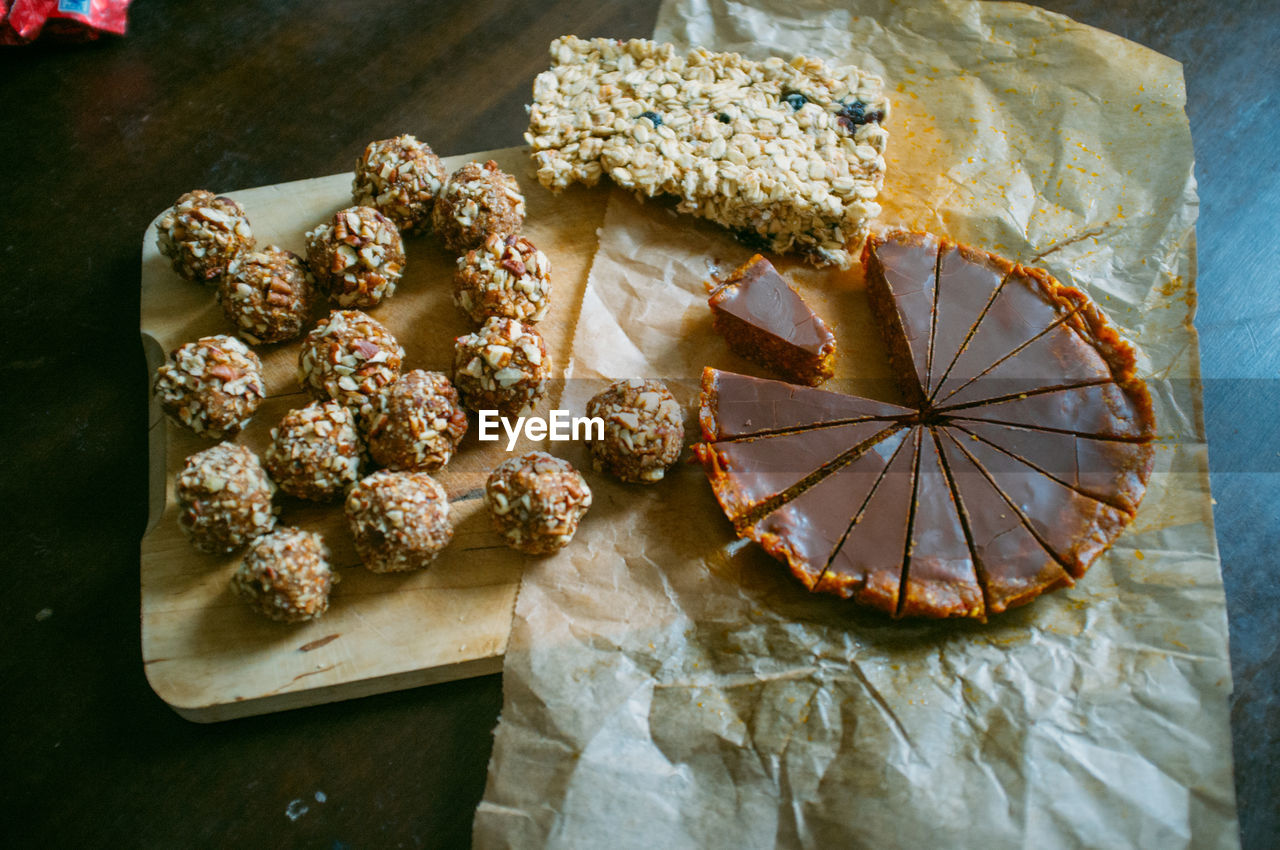 High Angle View Of Almond Balls And Chocolate Tart With Nut Bar On Table