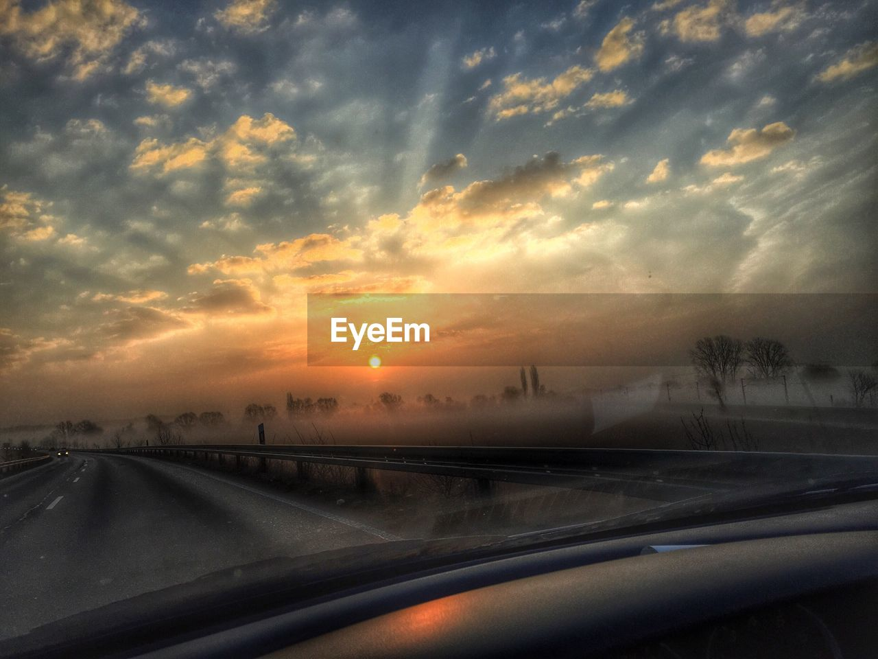 car, sunset, cloud - sky, transportation, sky, road, land vehicle, dramatic sky, windshield, car interior, nature, mode of transport, no people, car point of view, travel, beauty in nature, the way forward, motion, road trip, scenics, storm cloud, outdoors, day