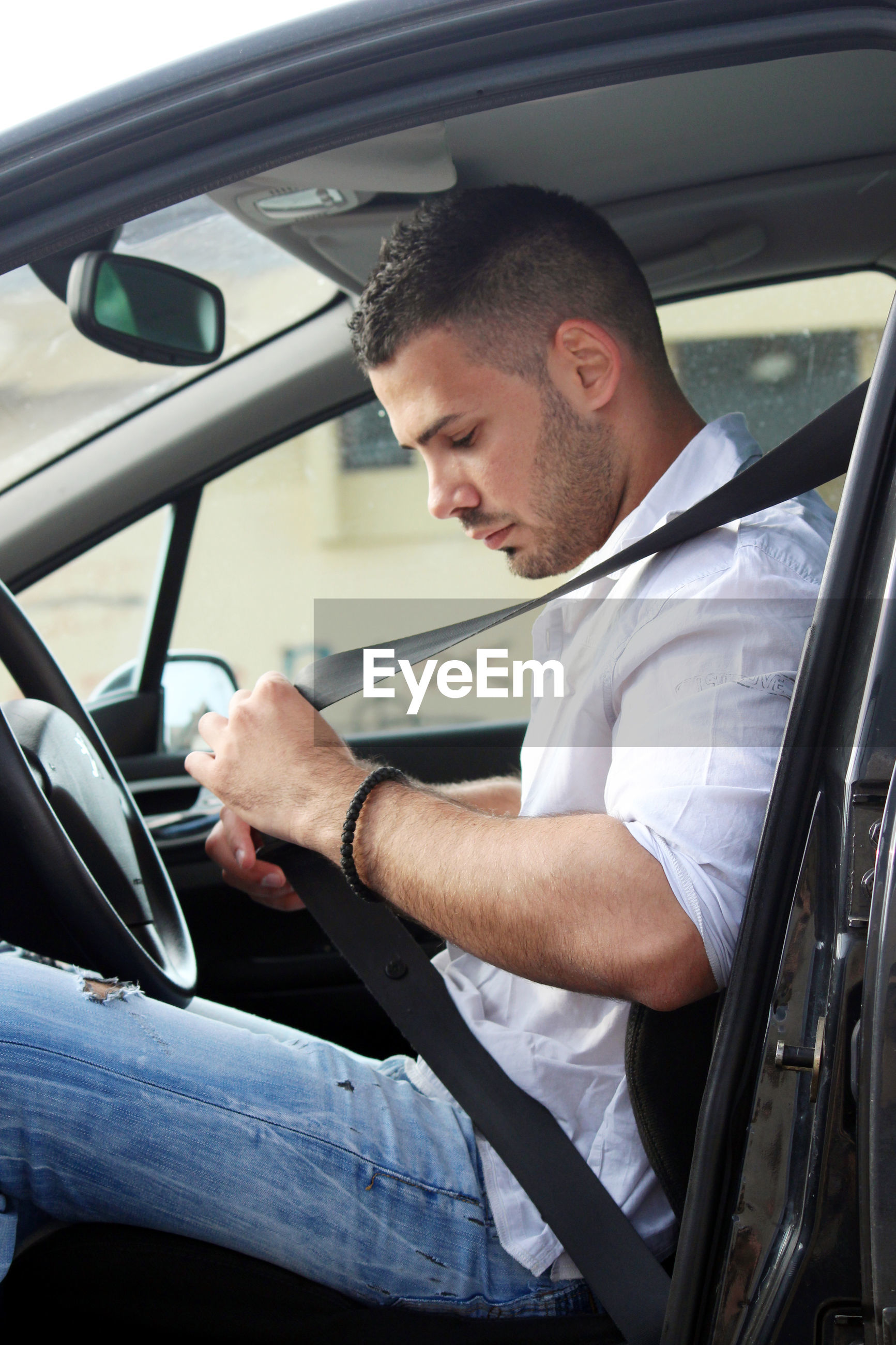 SIDE VIEW OF A MAN LOOKING THROUGH CAR