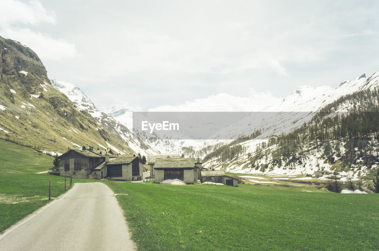 mountain, scenics, nature, beauty in nature, landscape, tranquil scene, sky, tranquility, mountain range, day, grass, no people, outdoors, the way forward, cloud - sky, snow, road, architecture, built structure, building exterior, tree