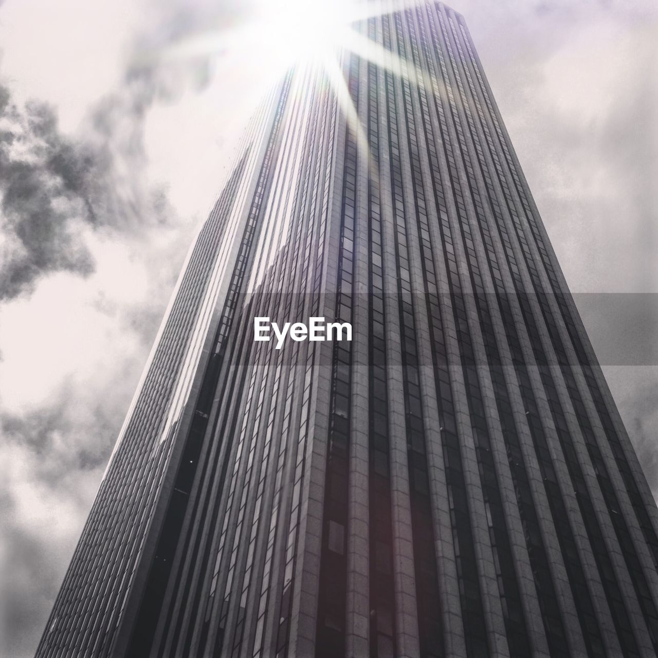 low angle view, built structure, architecture, building exterior, sky, modern, day, outdoors, skyscraper, sun, sunlight, no people, city