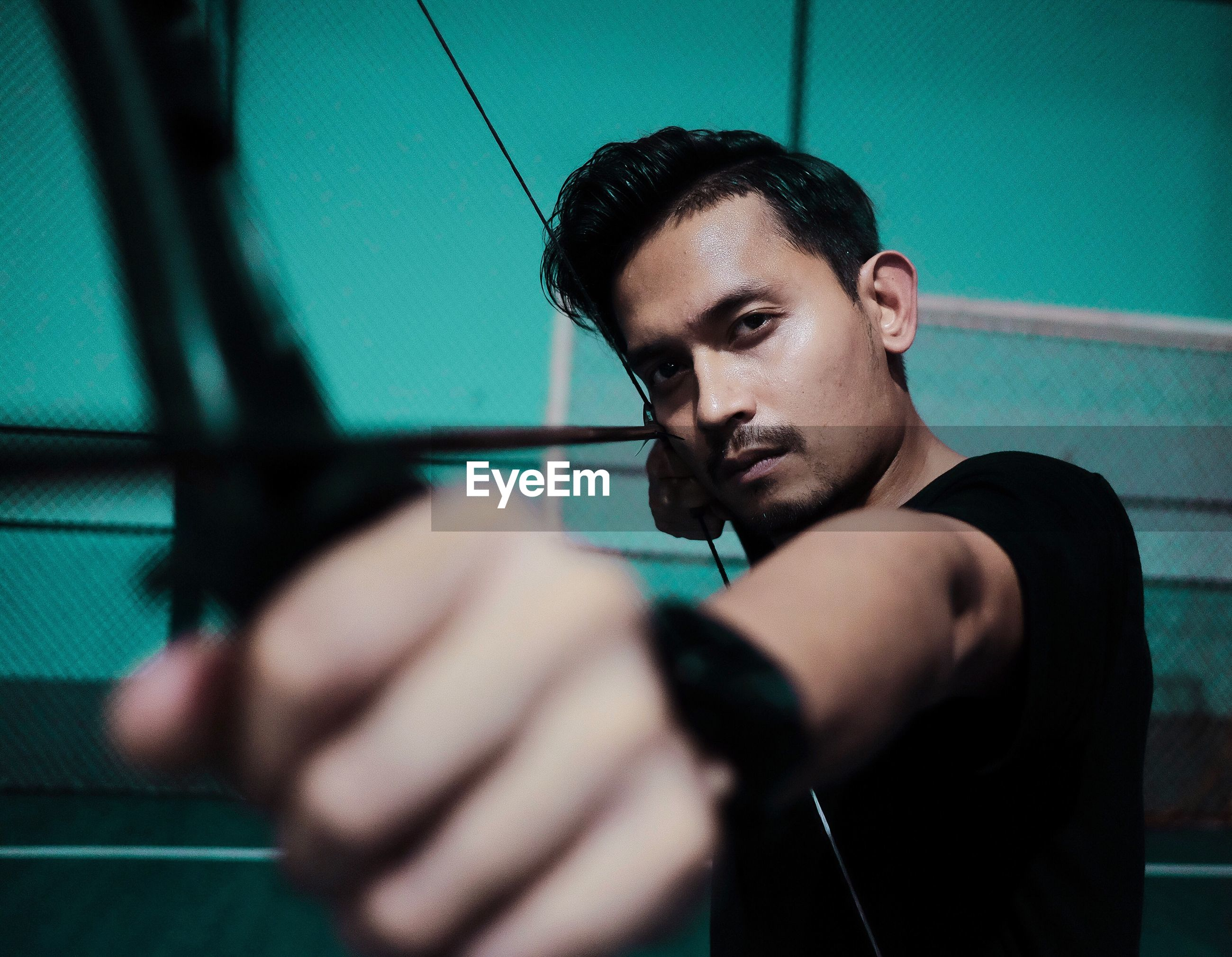 Portrait of young man holding bow and arrow