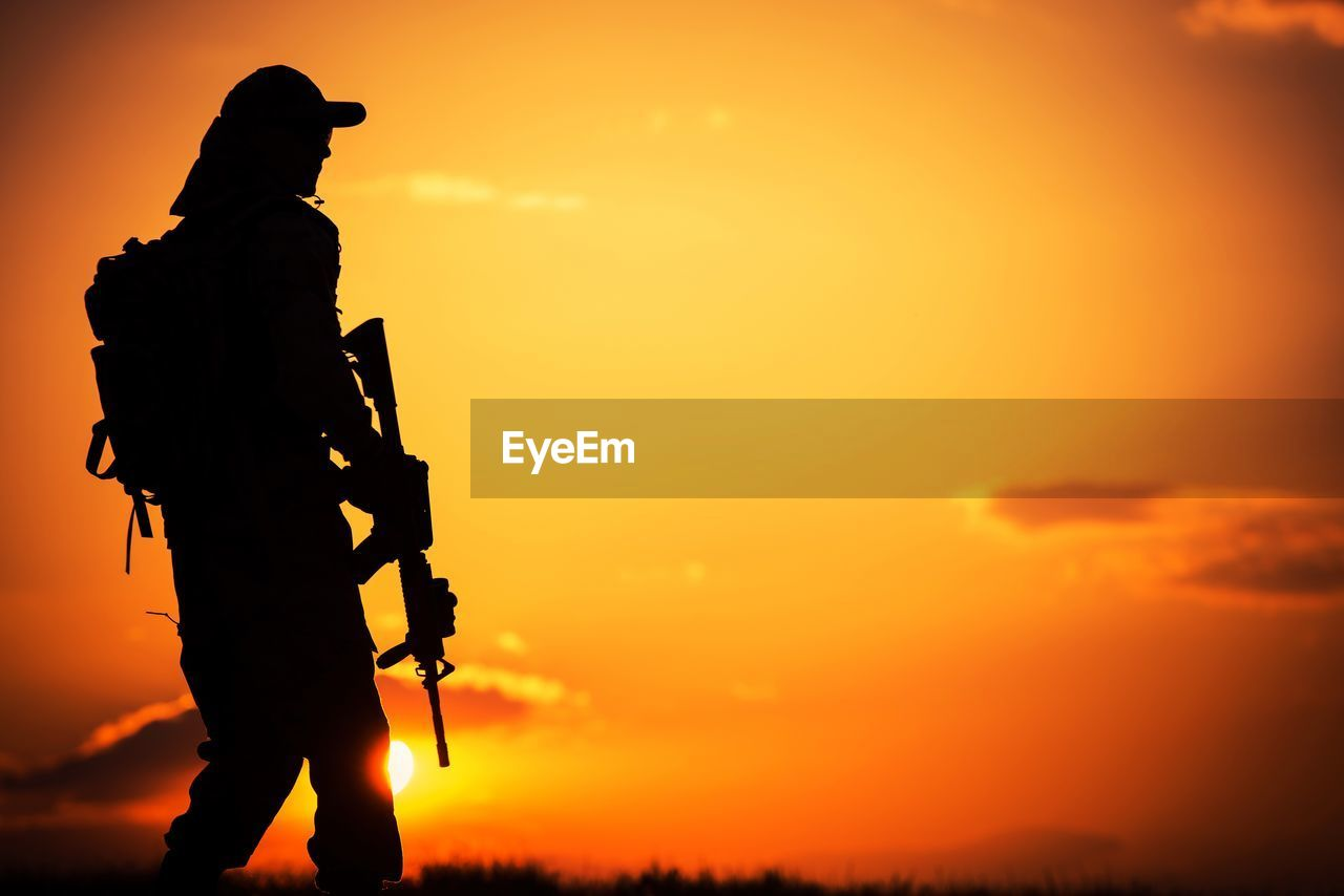 Silhouette Man With Rifle Walking Against Orange Sky During Sunset