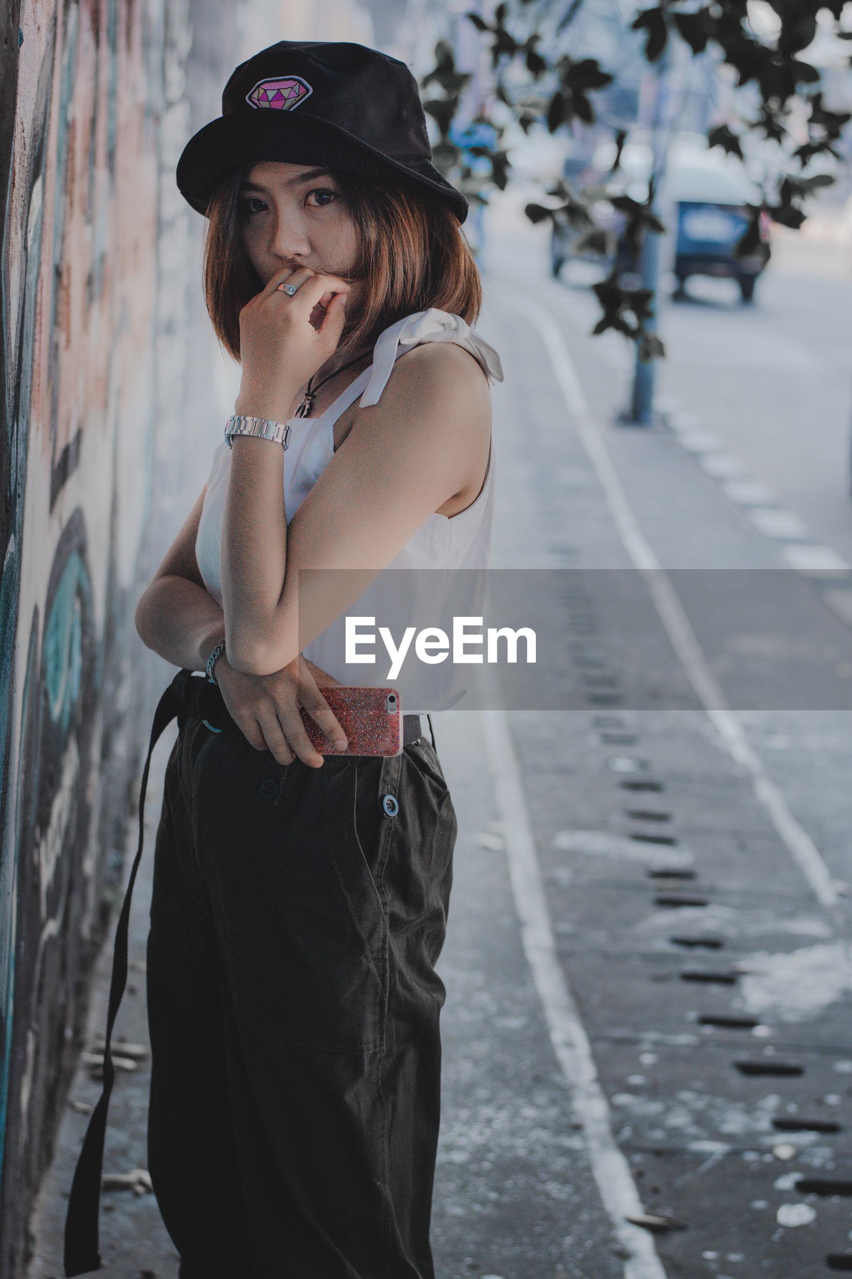 Portrait of woman standing on sidewalk in city