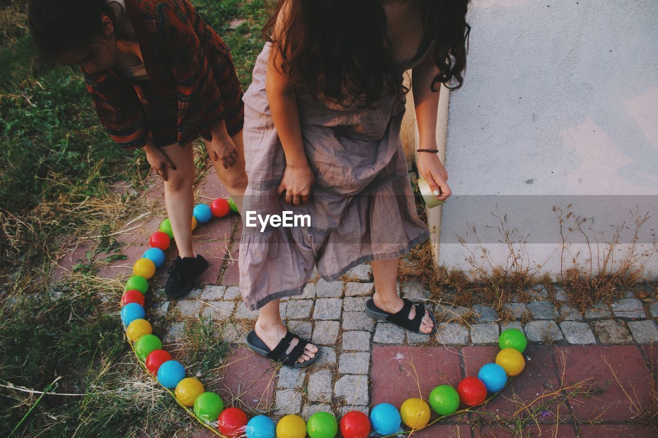 Women Arranging Multi Colored Balls In Yard